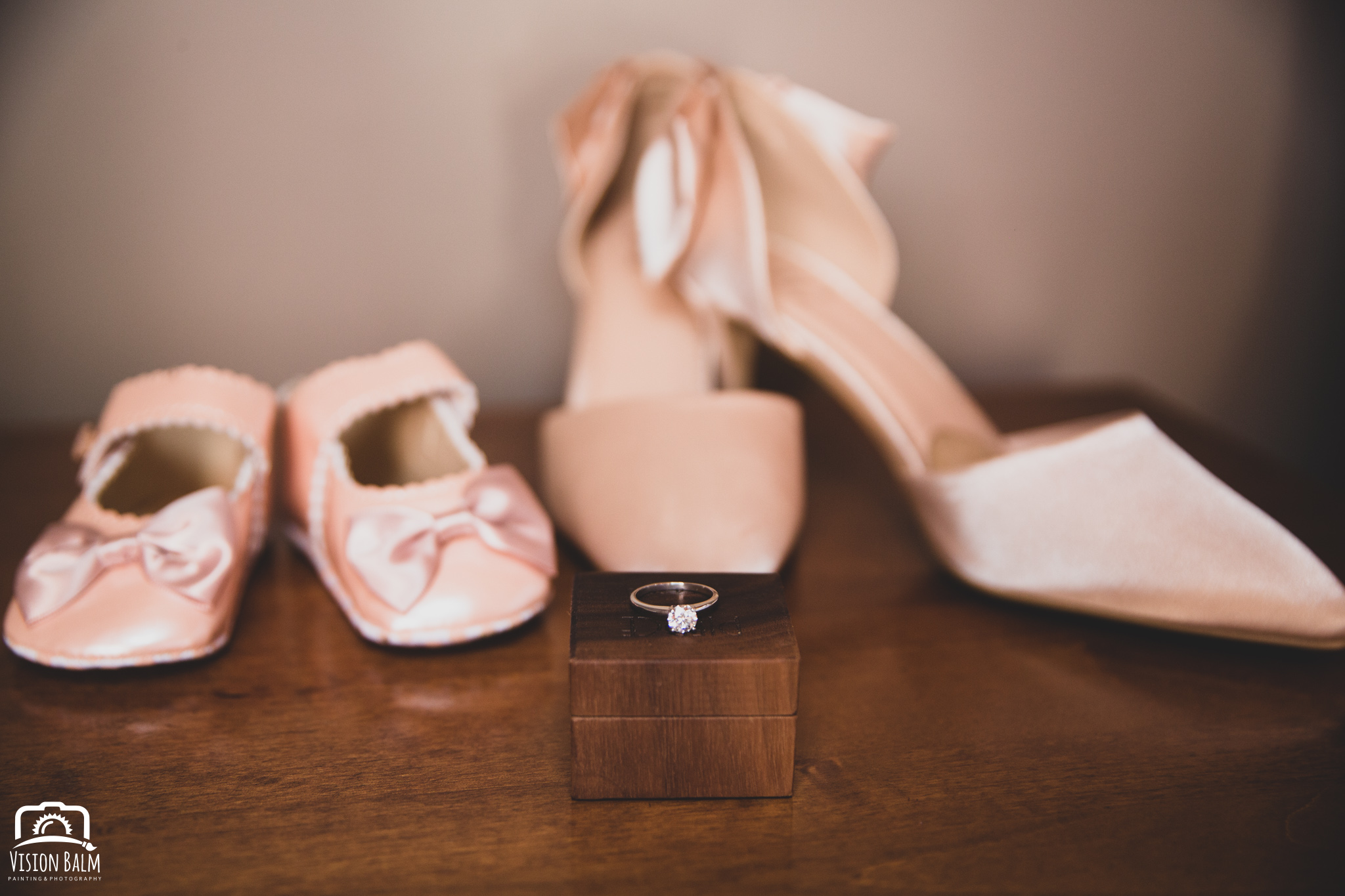 Detailed wedding photo of pink shoes with wedding ring in Zuka's Hilltop Barn by Vision Balm in Charleston, SC.