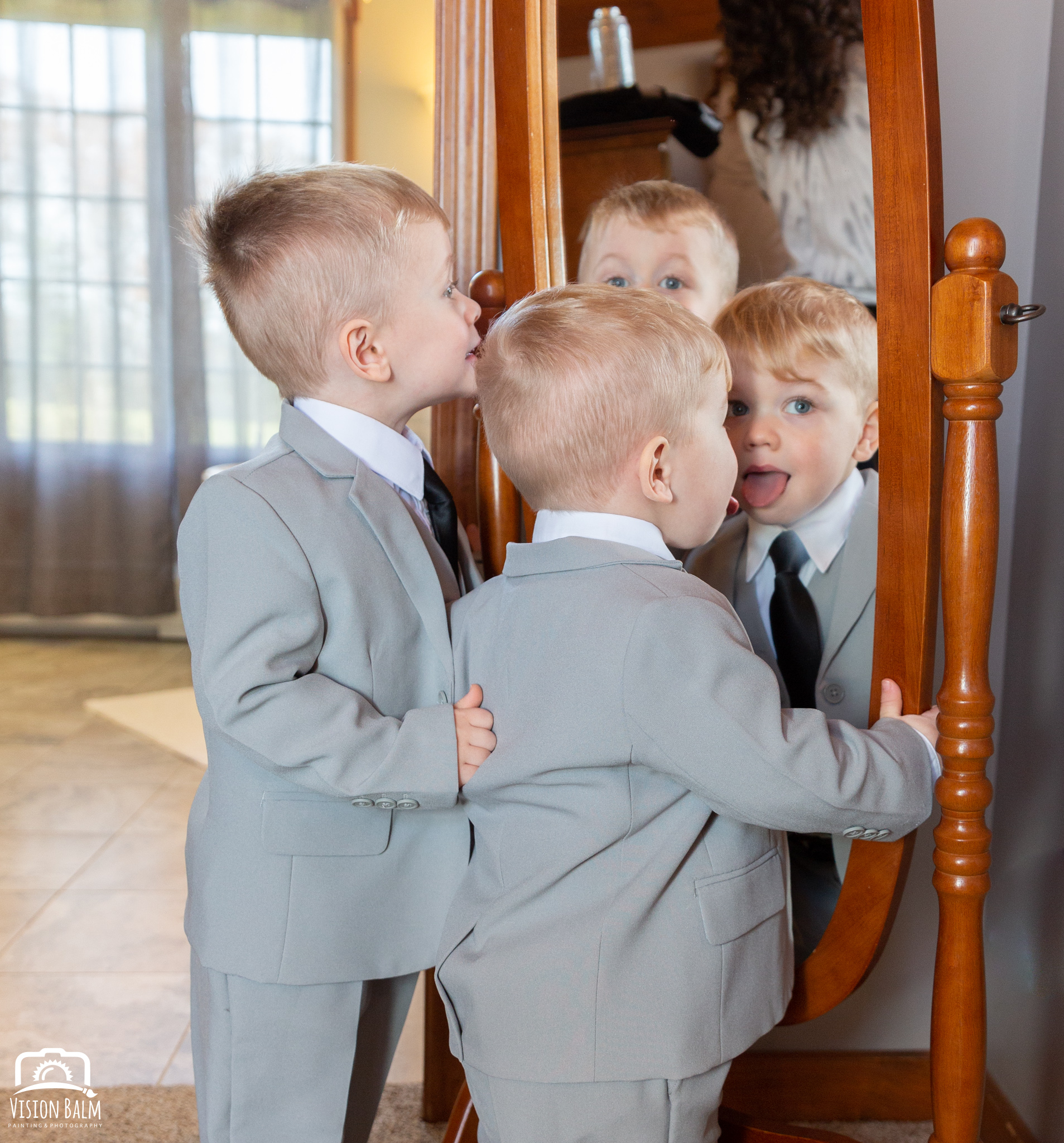 Portrait of young boys dressed in a gray suits for their mother's wedding looking at their reflections in the mirror in Zuka's Hilltop Barn by Vision Balm in Charleston, SC.