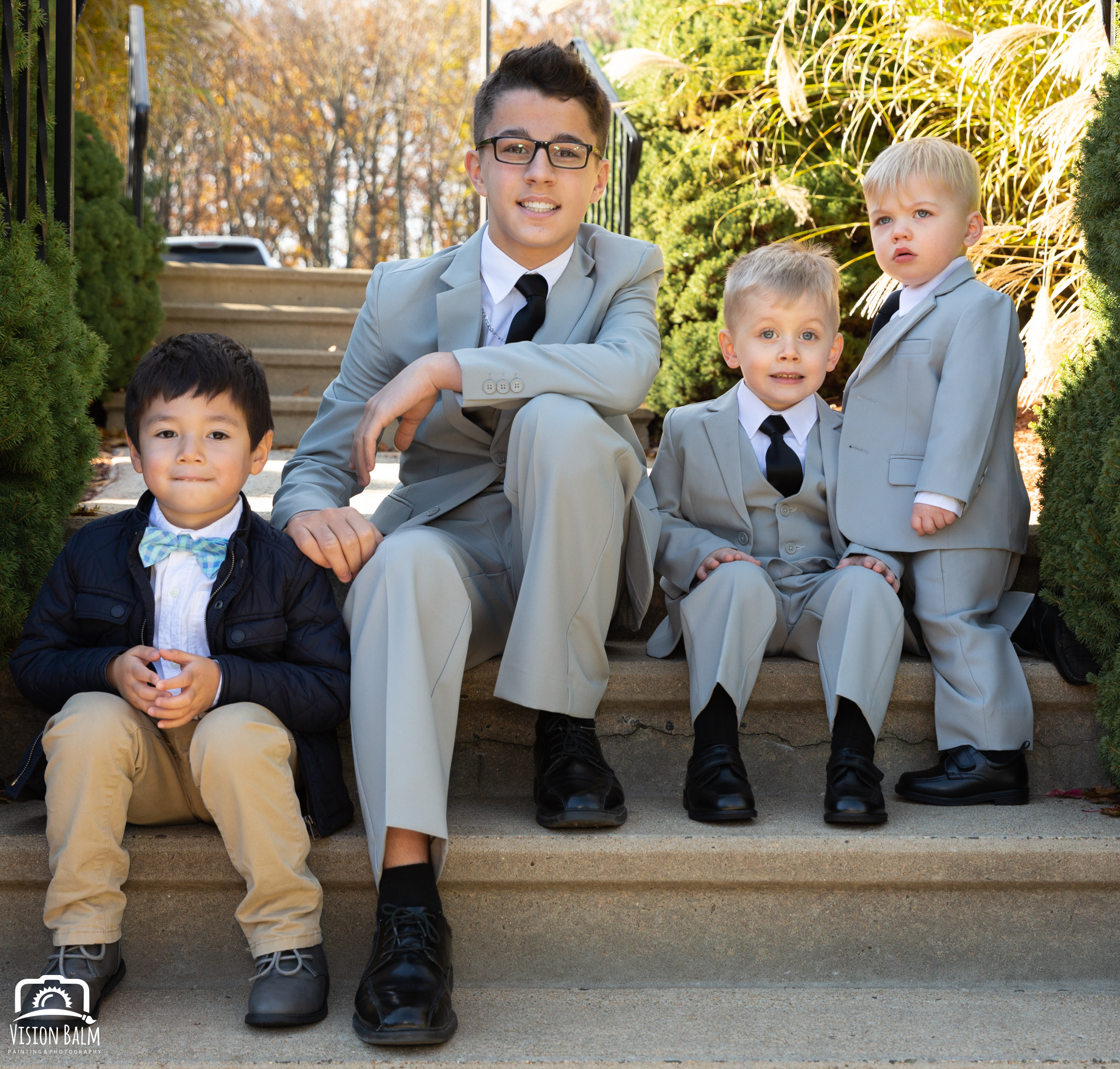 Lifestyle family photo of young boys in suits sitting on the stairs before wedding in Zuka's Hilltop Barn by Vision Balm in Charleston, SC.