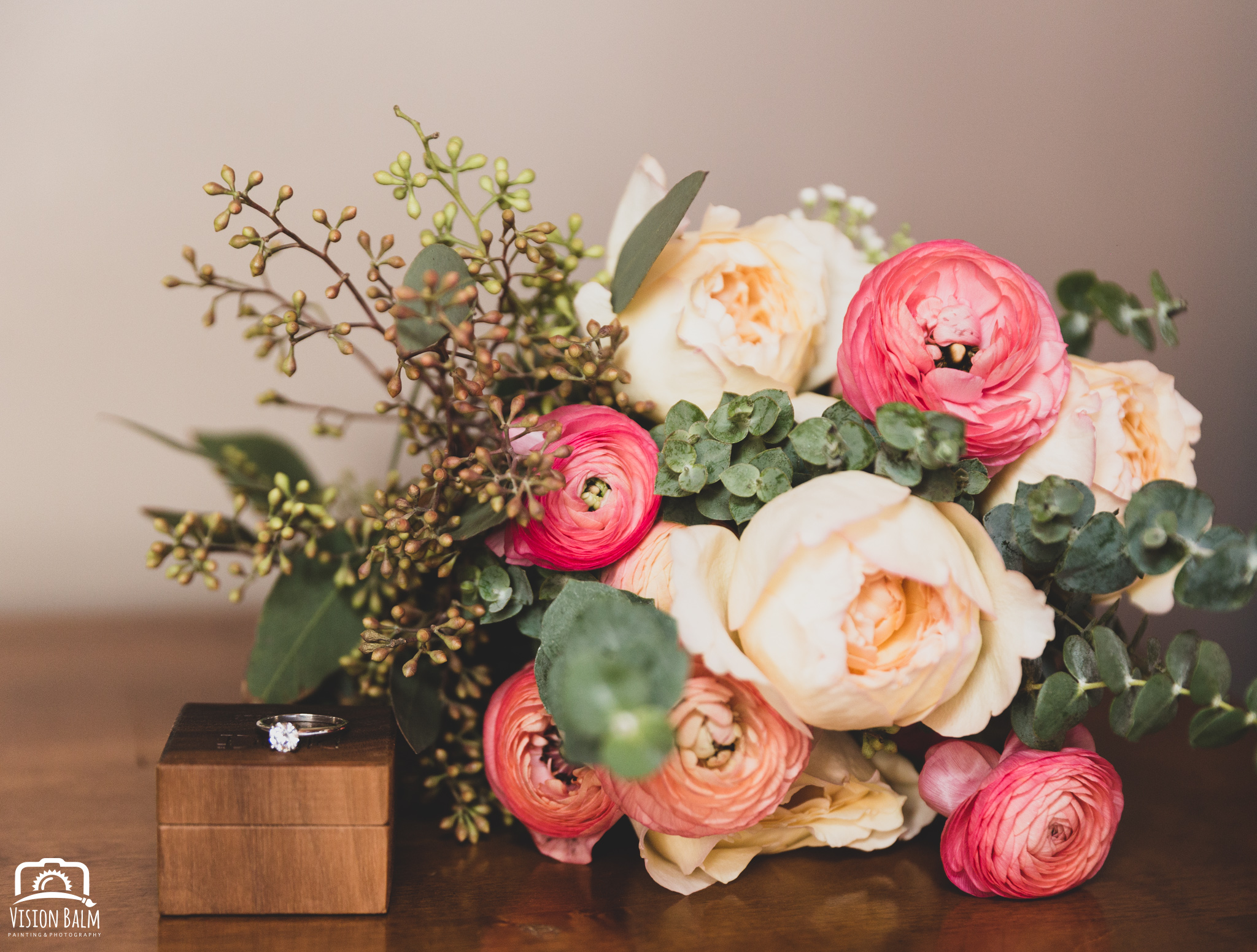 Wedding photo of bouquet of flowers next to wedding ring in Zuka's Hilltop Barn by Vision Balm in Charleston, SC.