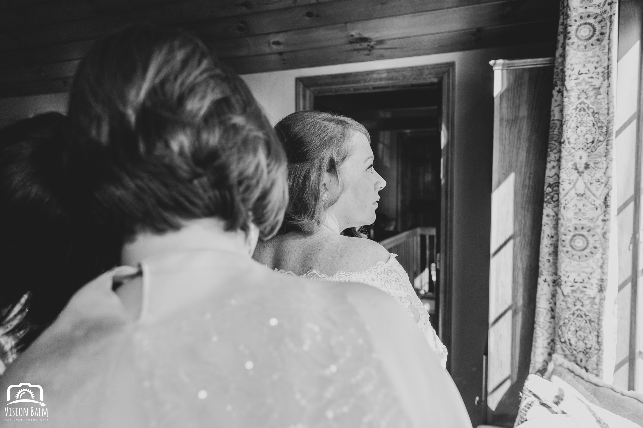 Lifestyle wedding photo of bride and her mother helping her put on her wedding dress in Zuka's Hilltop Barn by Vision Balm in Charleston, SC.