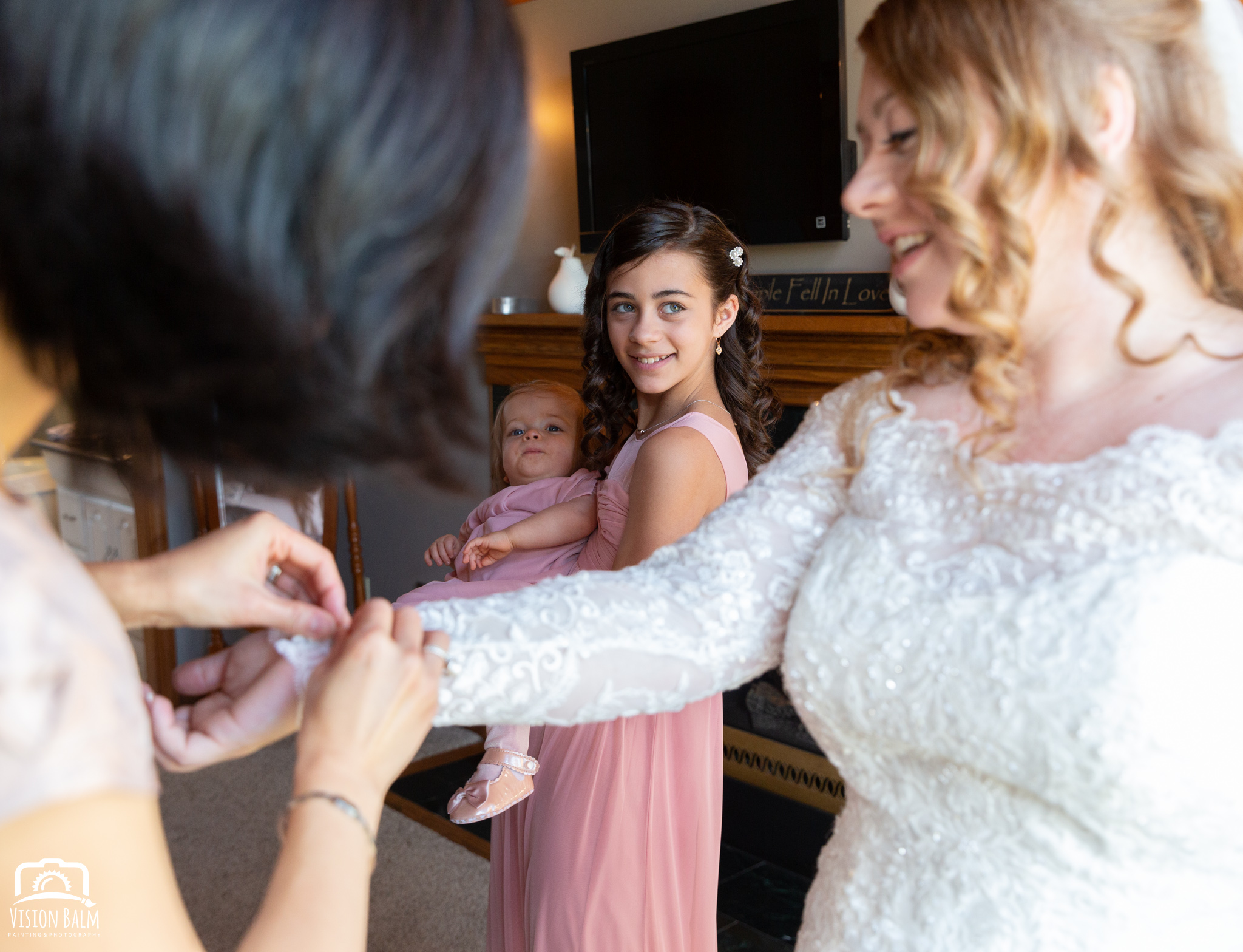 Lifestyle wedding photo of bride getting help with her dress in Zuka's Hilltop Barn by Vision Balm in Charleston, SC.