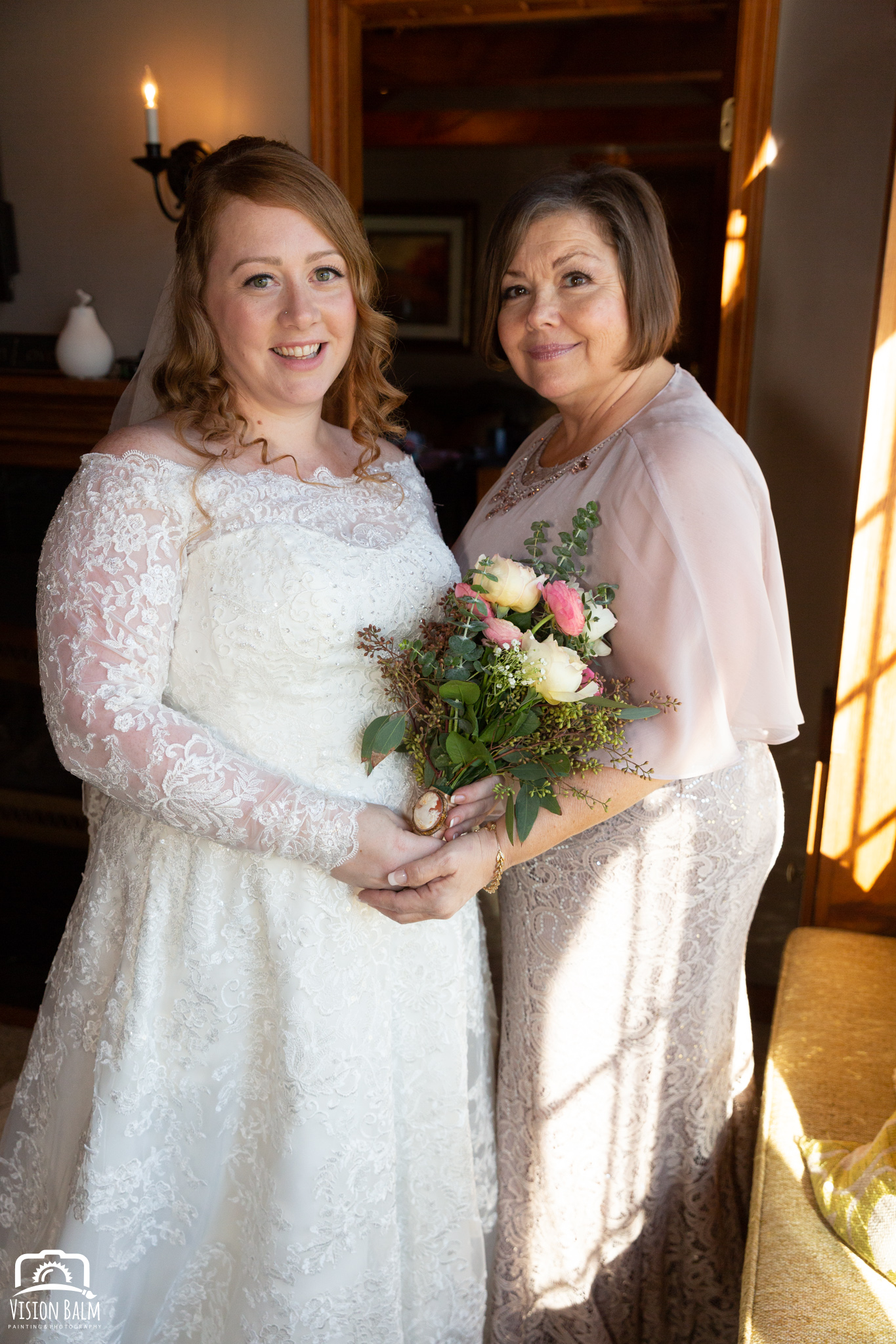 Lifestyle wedding photo of bride and her mom in Zuka's Hilltop Barn by Vision Balm in Charleston, SC.