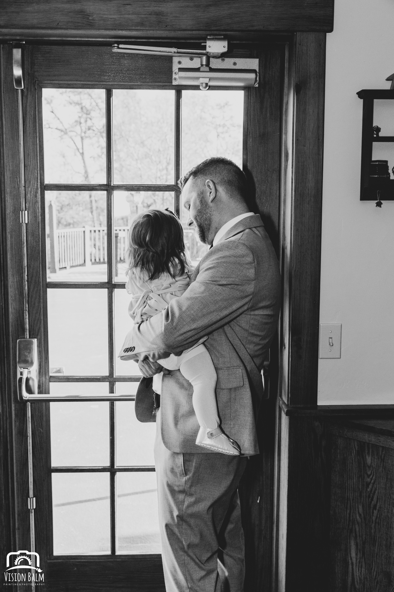 Lifestyle wedding photo of groom and his baby daughter in Zuka's Hilltop Barn by Vision Balm in Charleston, SC.