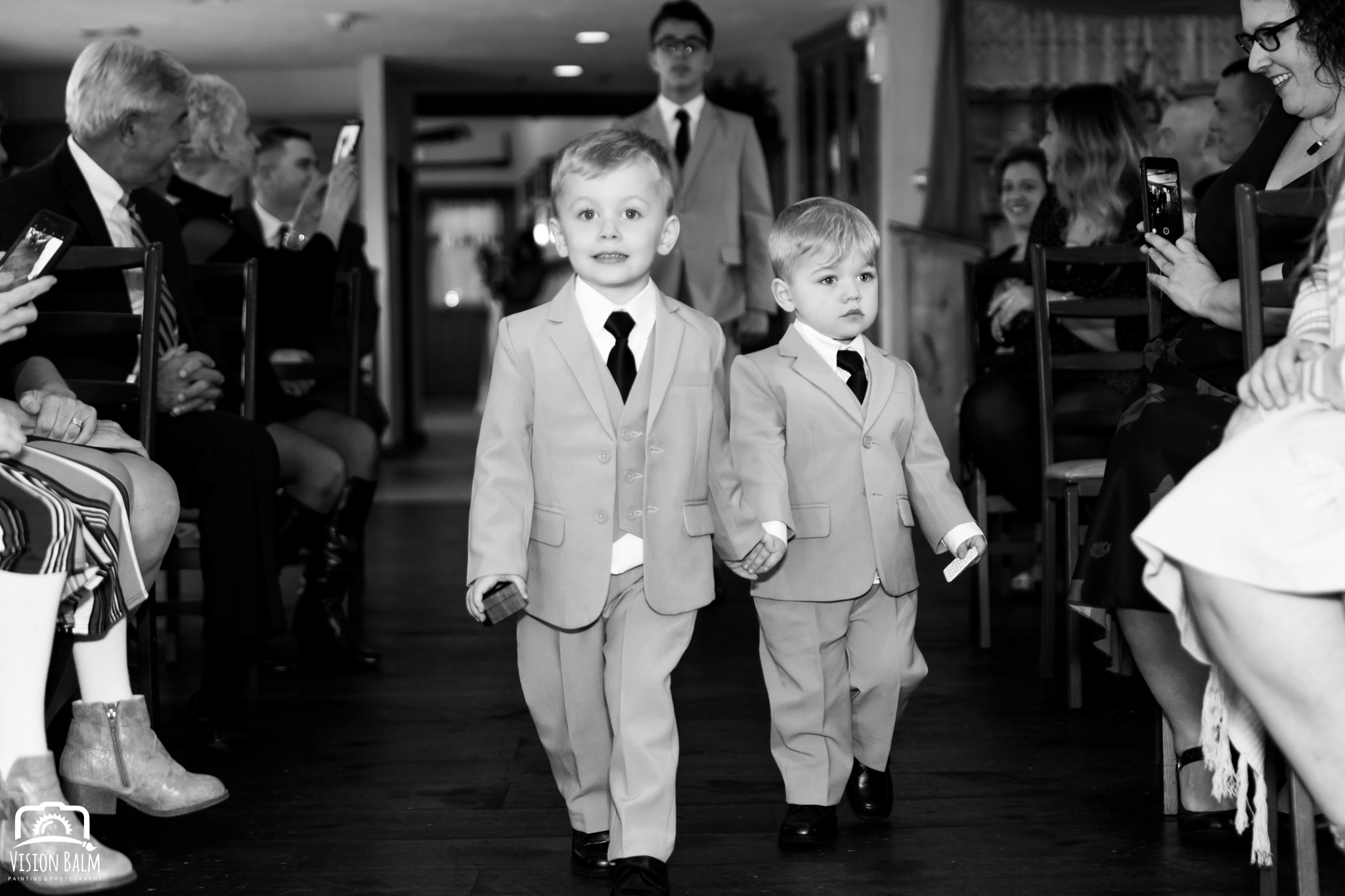 Lifestyle wedding photo of sons of bride in suits walking down the aisle in Zuka's Hilltop Barn by Vision Balm in Charleston, SC.