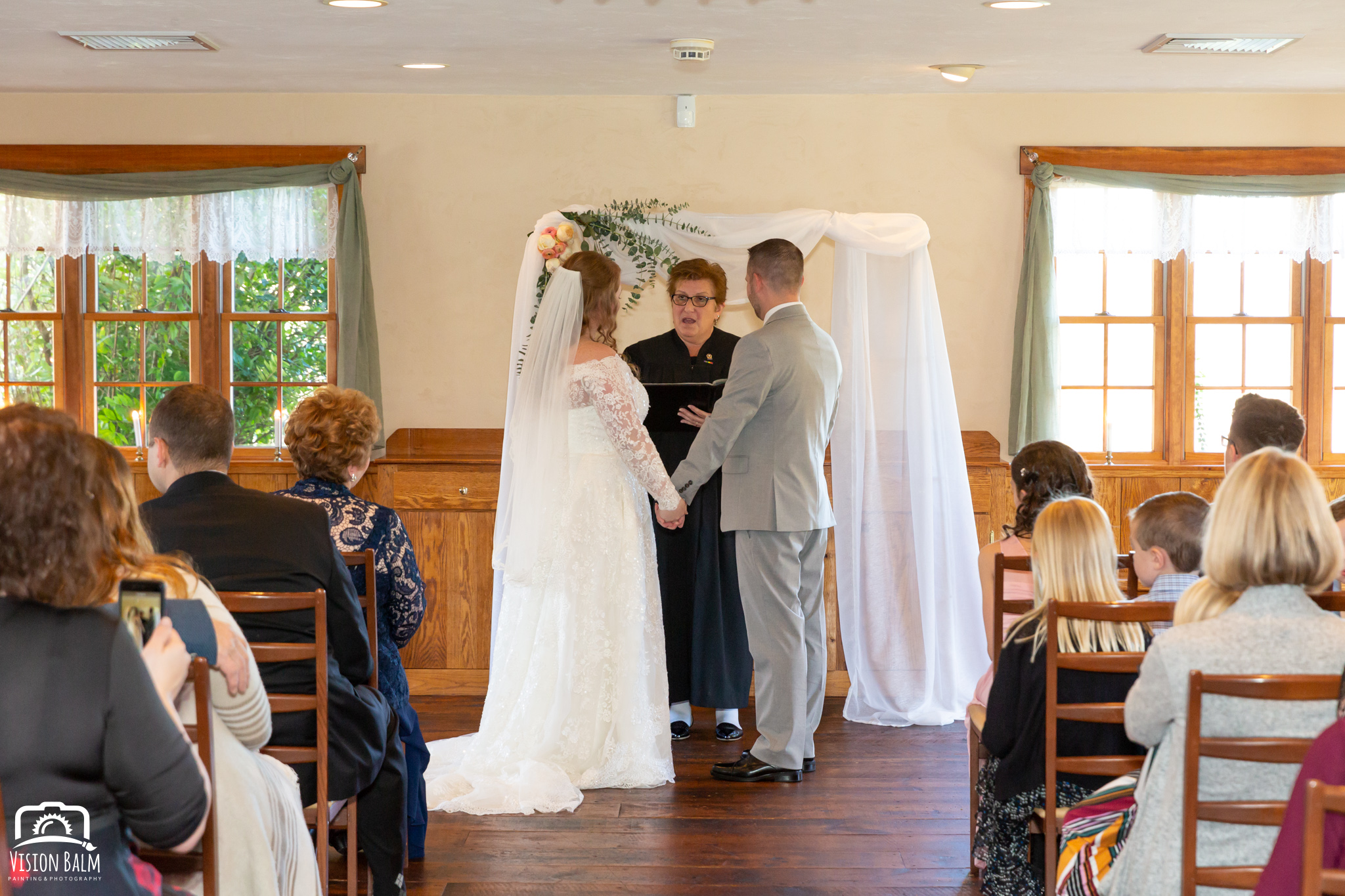 Wedding photo of bride and groom holding hands at the ceremony in Zuka's Hilltop Barn by Vision Balm in Charleston, SC.