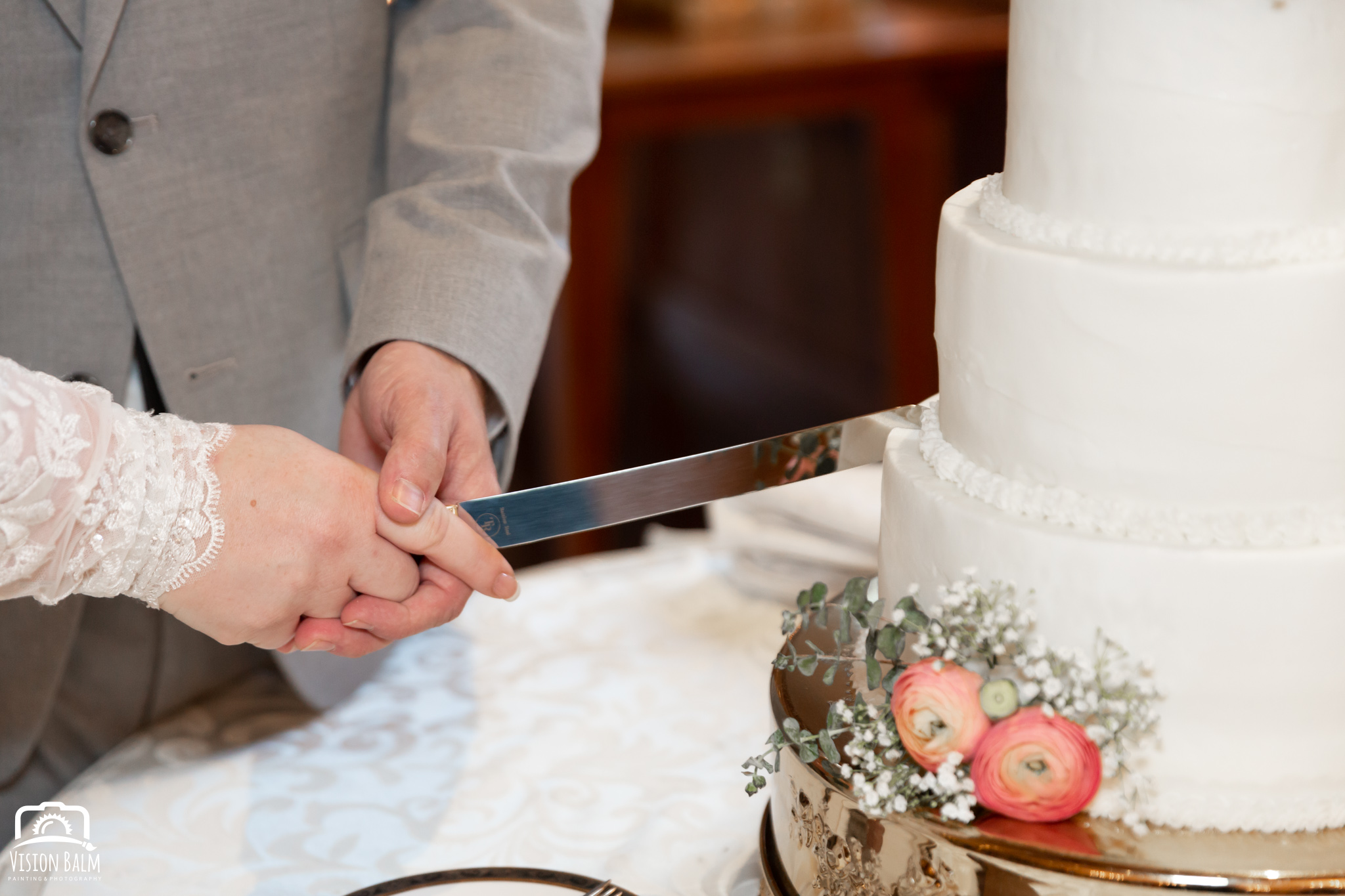 Wedding photo of groom and bride cutting the wedding cake in the venue of Zuka's Hilltop Barn by Vision Balm in Charleston, SC.