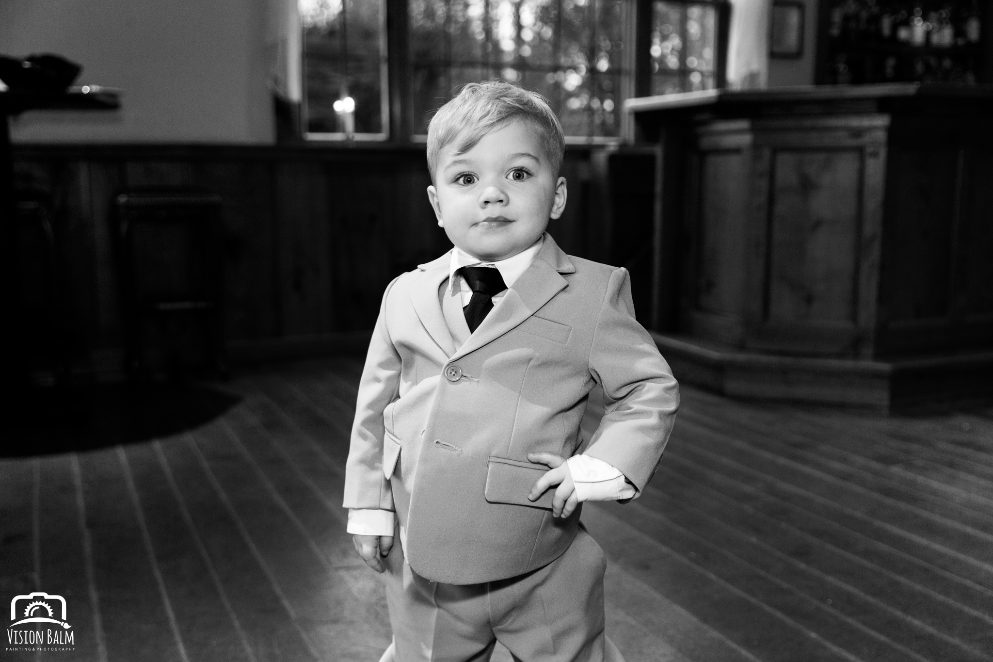 Wedding photo of bride's son in a suite posing for the camera in Zuka's Hilltop Barn by Vision Balm in Charleston, SC.