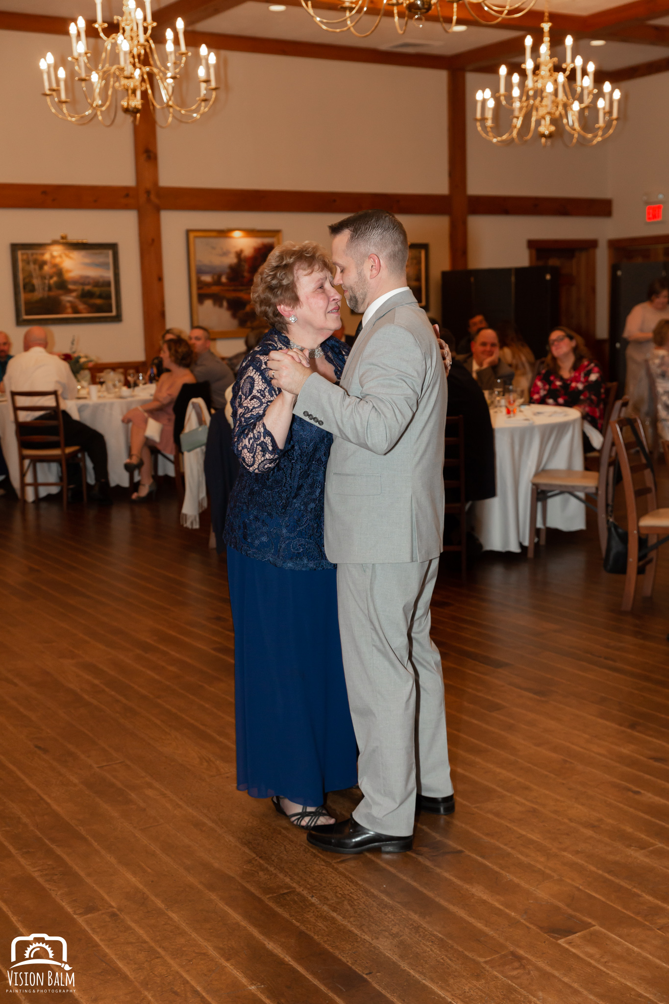 Wedding photo of groom and his mother dancing in the venue of Zuka's Hilltop Barn by Vision Balm in Charleston, SC.