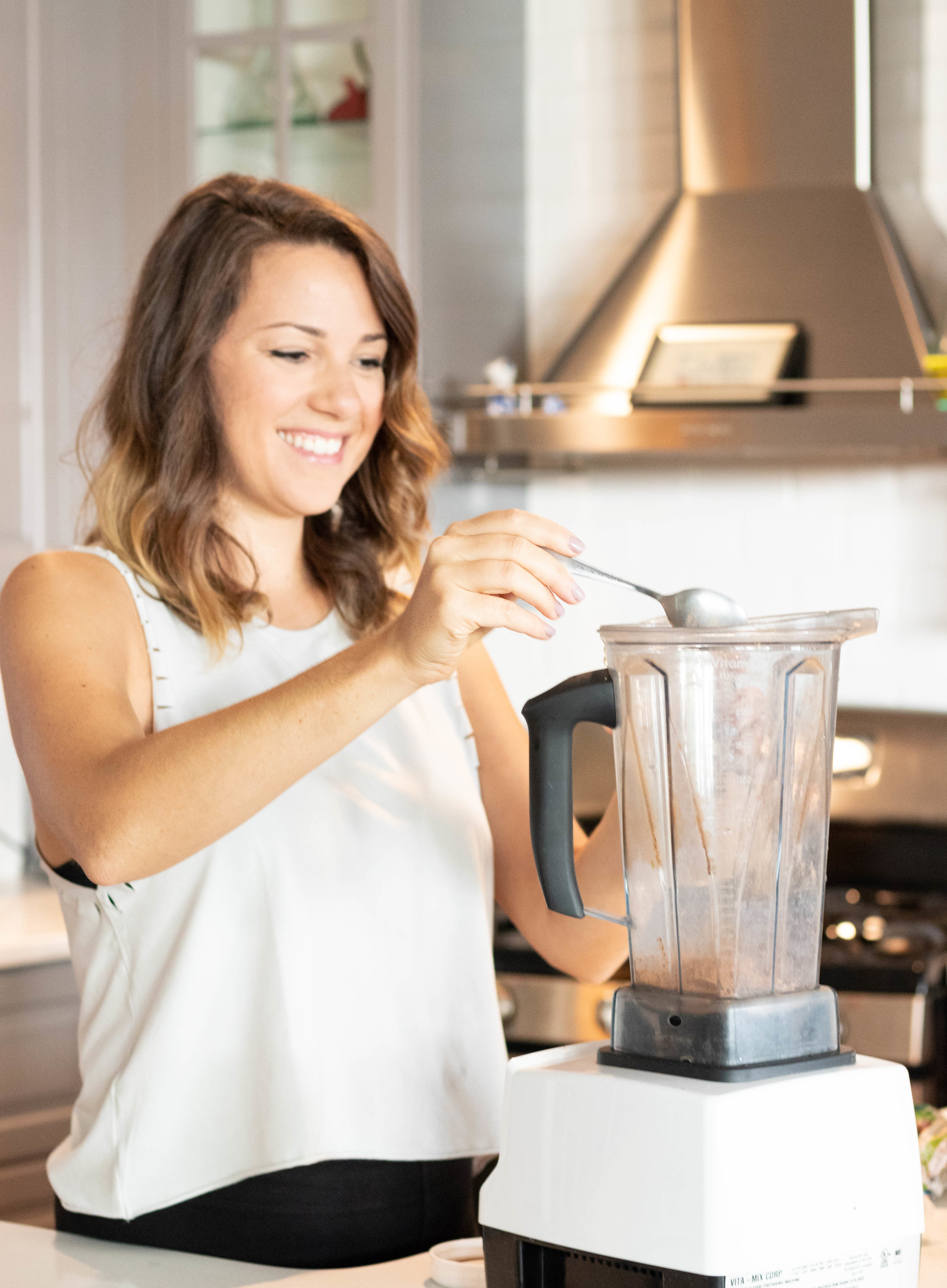 Professional lifestyle portrait of Natasha Wellness health coach making a smoothie in kitchen photographed by Vision Balm in Charleston, SC.
