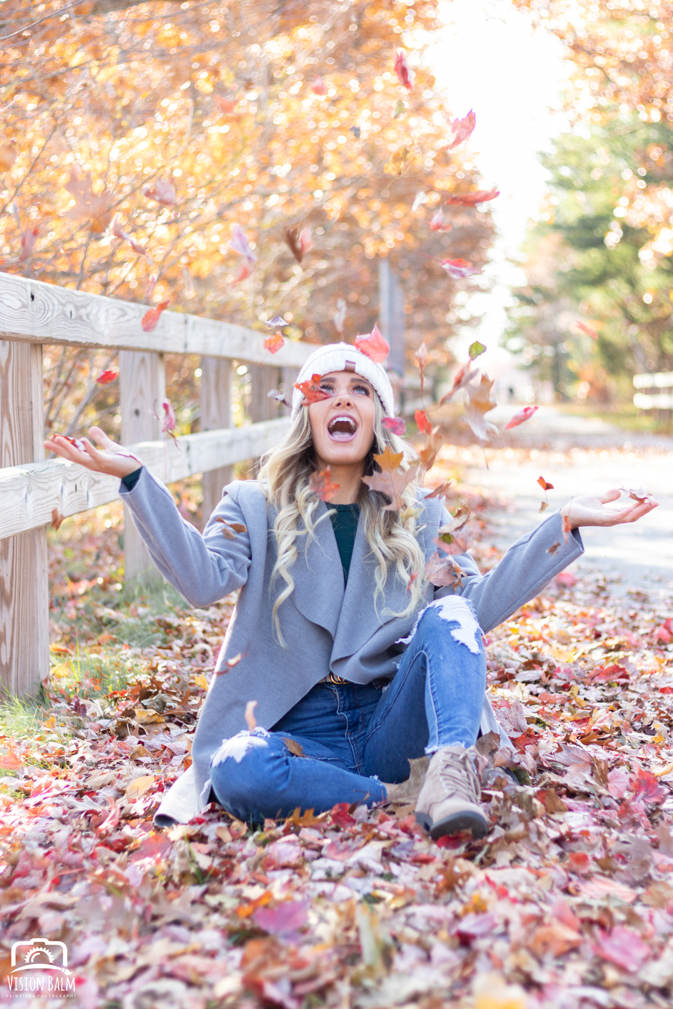Professional fall portrait photography of model wearing a knit hat and jacket throwing leaves in the air photographed by Vision Balm in Charleston, SC.