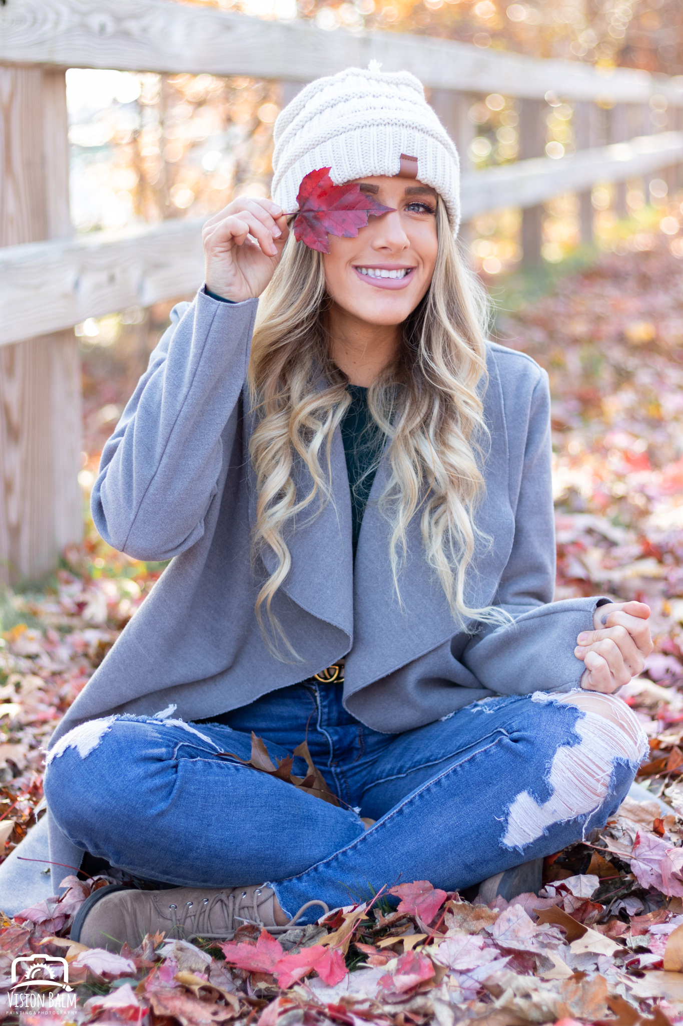 Professional fall portrait photography of model wearing a knit hat holding a red leaf photographed by Vision Balm in Charleston, SC.