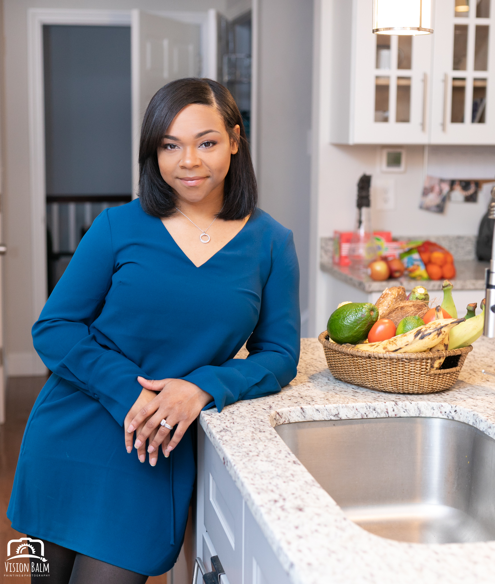 Professional portrait of a registered dietitian leaning on the counter top in the kitchen and wearing a blue dress photographed by Vision Balm in Charleston, SC.