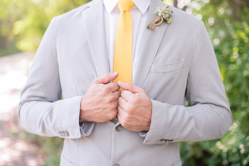 groom in bohemian outfit and succulent