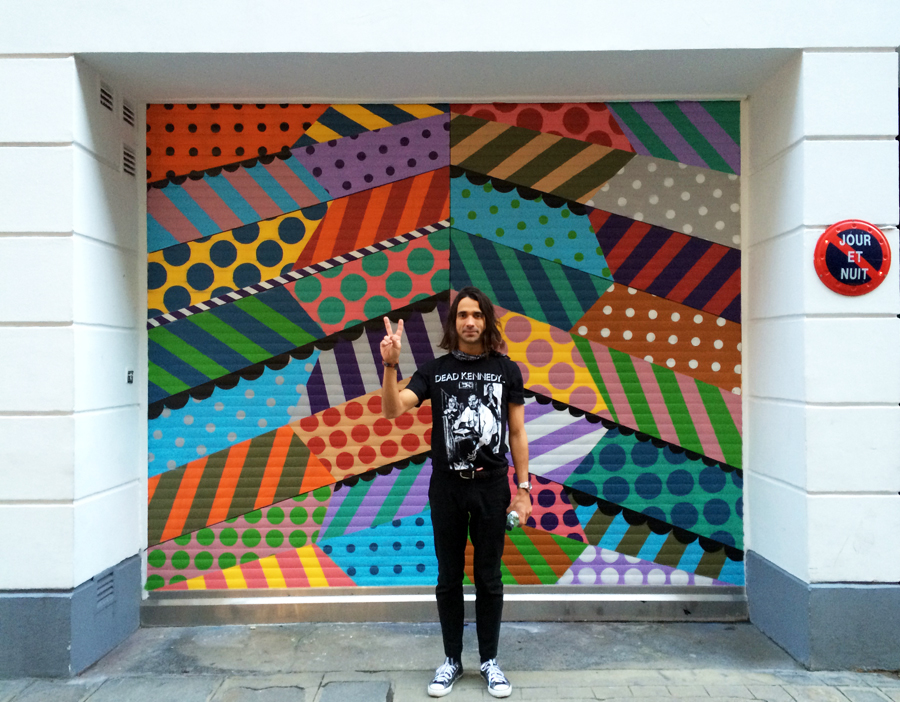 Jason, pictured in front of a mural he painted in Paris.