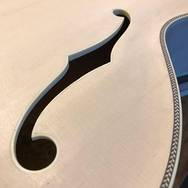 "Binding the ""f"" holes is tricky when the guitar is otherwise fully constructed. But to get the maximum volume from the guitar, you have to do the final shaping of the holes with the guitar strung and tunes to pitch. So binding has to wait until this essential step has been done. . . . #guitarcollector #archtop  #semiacoustic #guitarshop #guitar #electricguitar #bluesplayer #jazzguitar #bluesguitarist #uniqueguitar #guitarists #guitarcover #guitarphotography #guitarporn #rockguitarist #talentedmusicians #rockshows #rockstarguitar  #gibson #fender #woodworkerplanet #woodworking #handmadeinamerica #guitarconnoisseur"