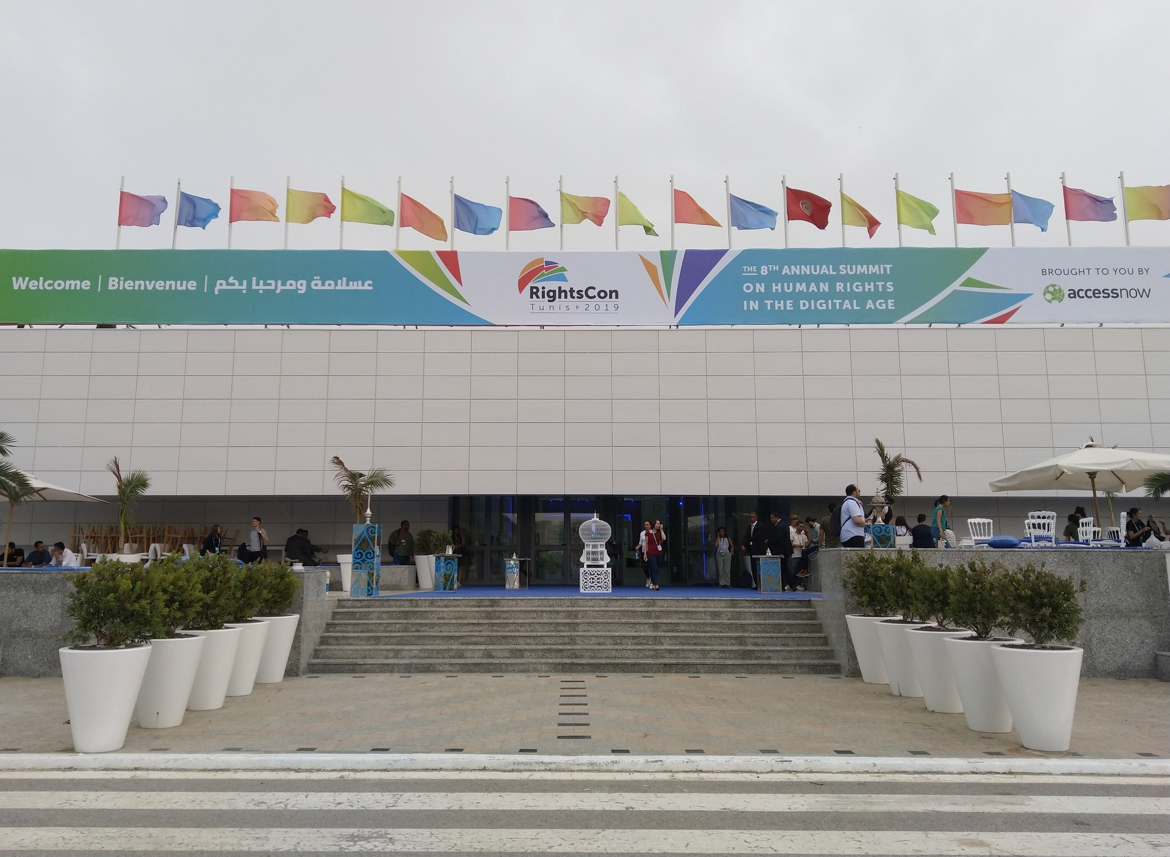"""Picture showing the main entrance of the RightsCon conference venue, with a big banner over it stating """"RightsCon Tunis 2019"""" and """"8th annual summit on human rights in the digital age"""". Flags on top in various colors, as well as a Tunisian flag. Photo: Private/Lisa-Marie M. Selvik."""