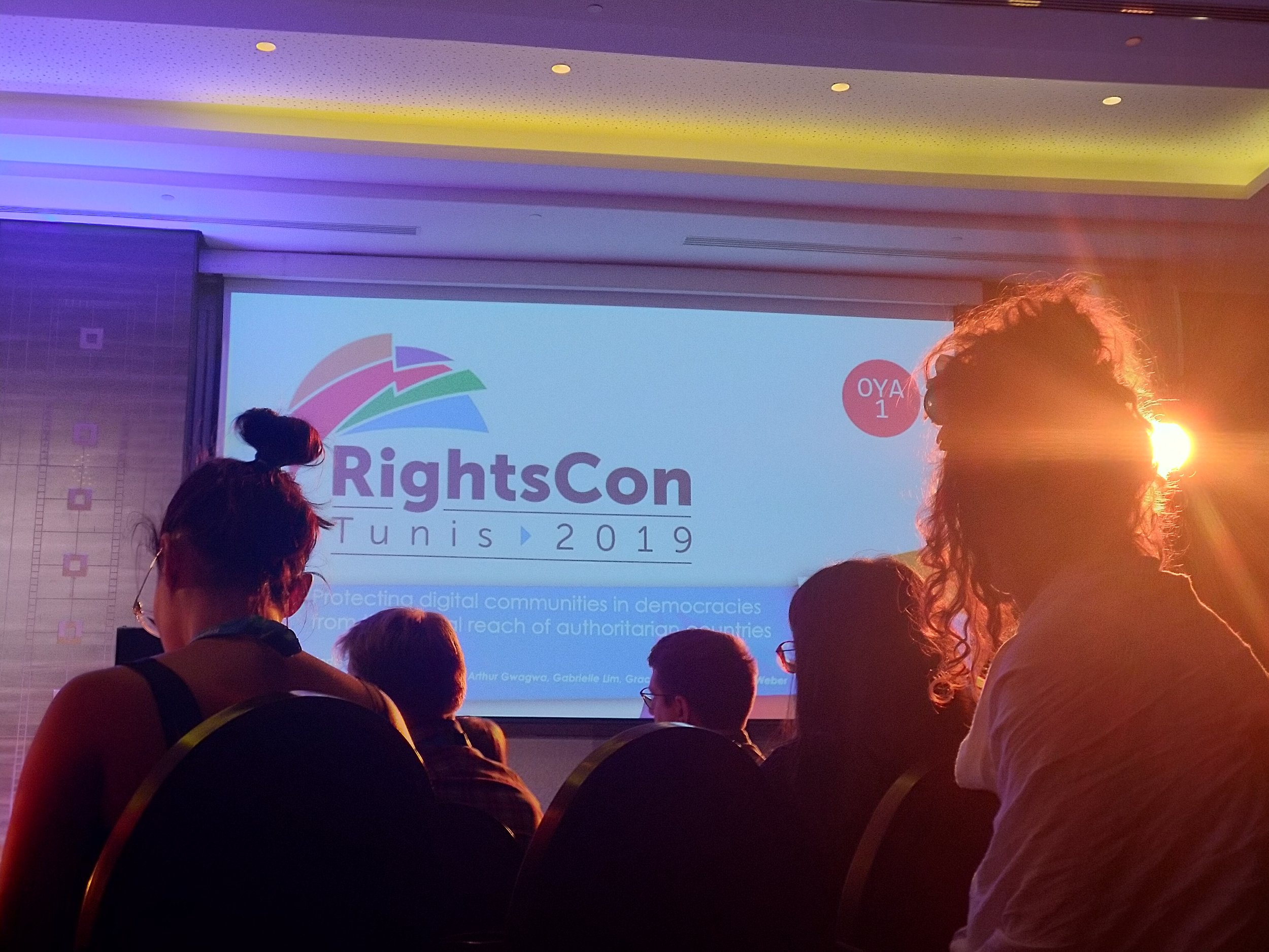 """Picture showing a big canvas displaying the topic of a session, captured from the back, with people in the foreground and a beam of light streaming through a girls hair from the podium. The projected image on the canvas reads """"RightsCon Tunis 2019"""" and """"Protecting digital communities in democracies from the digital reach of authoritarian countries"""". Photo: Private/Lisa-Marie M. Selvik."""