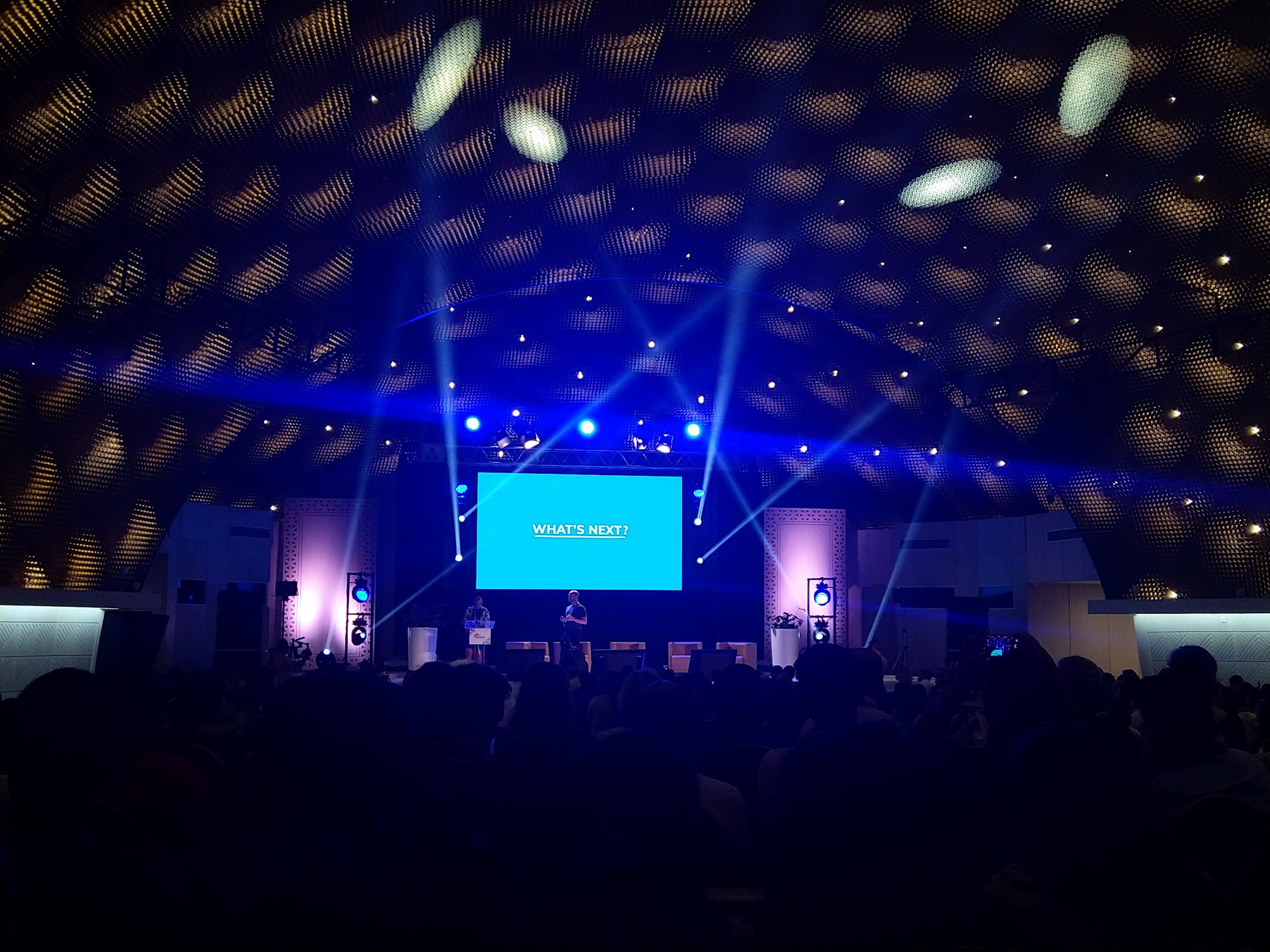"""Picture showing the main stage at the closing ceremony, in a massive hall called The Beehive due to its shape and light settings. The big canvas on the stage reads in bold, capital letters: """"What's next?"""". Photo: Private/Lisa-Marie M. Selvik."""