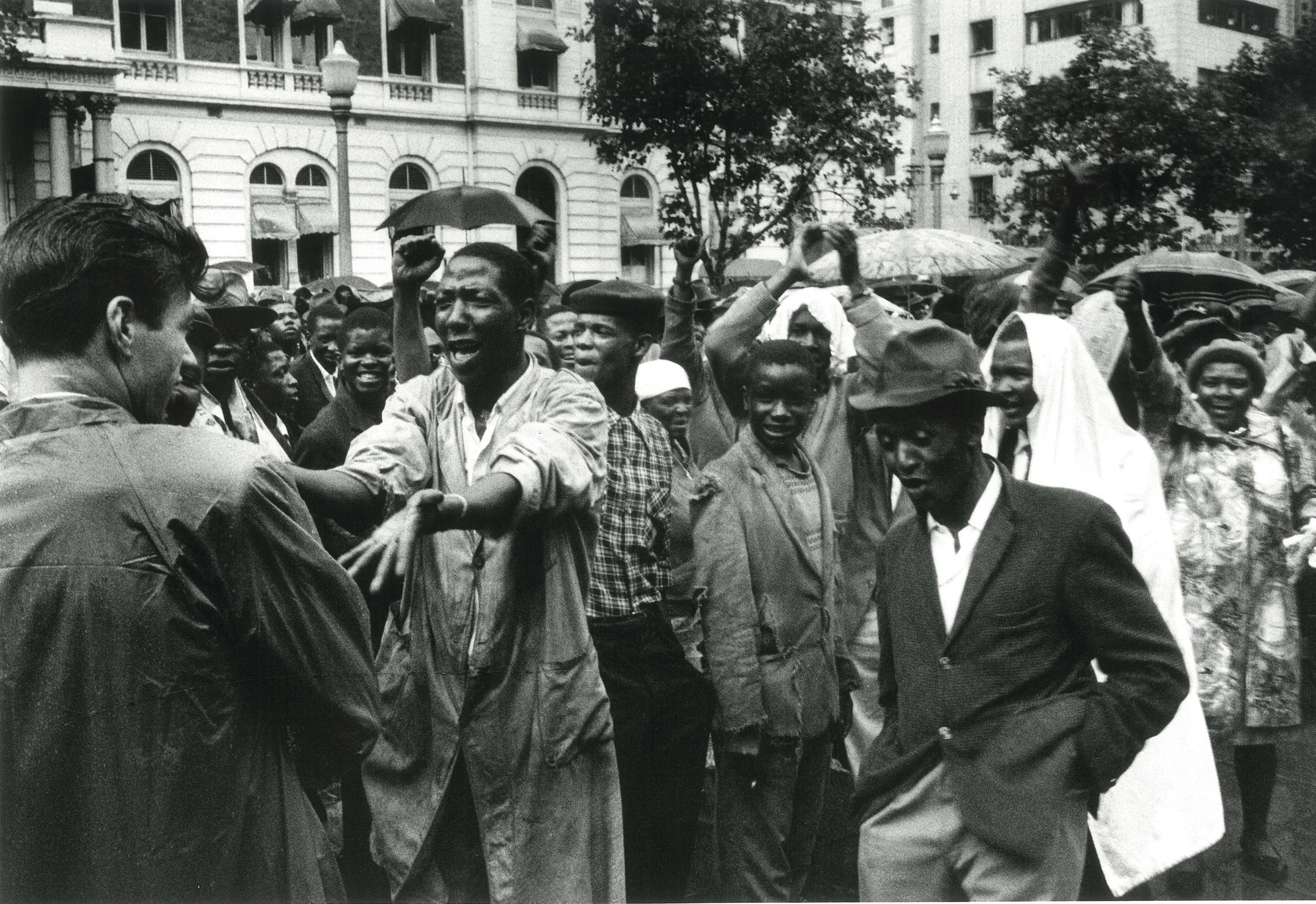 1960 – Africans at the Congress of Democrats rally in the rain, outside Johannesburg Town Hall   Courtesy of the Estate of John Goldblatt
