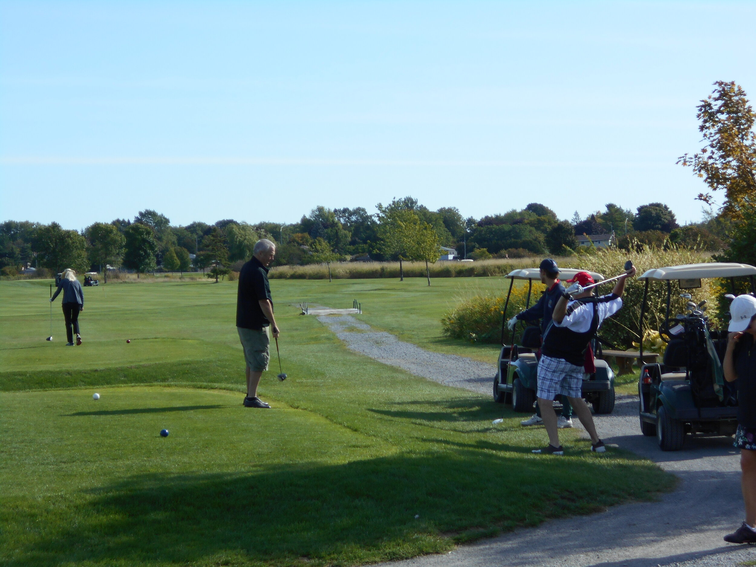 """manja going to retrieve farley's tee shot off the first hole; ray stretching to make sure he can hit his just a wee bit further than dave's 30 yarder. riley, my stepson, thinking, """"whoa, maybe i am going to have to carry these 60-somethings"""""""