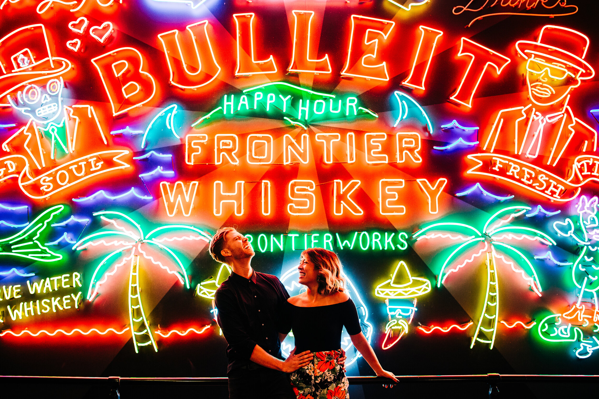 Couple laughing in front of Bulleit Whiskey neon sign at Grand Central Market
