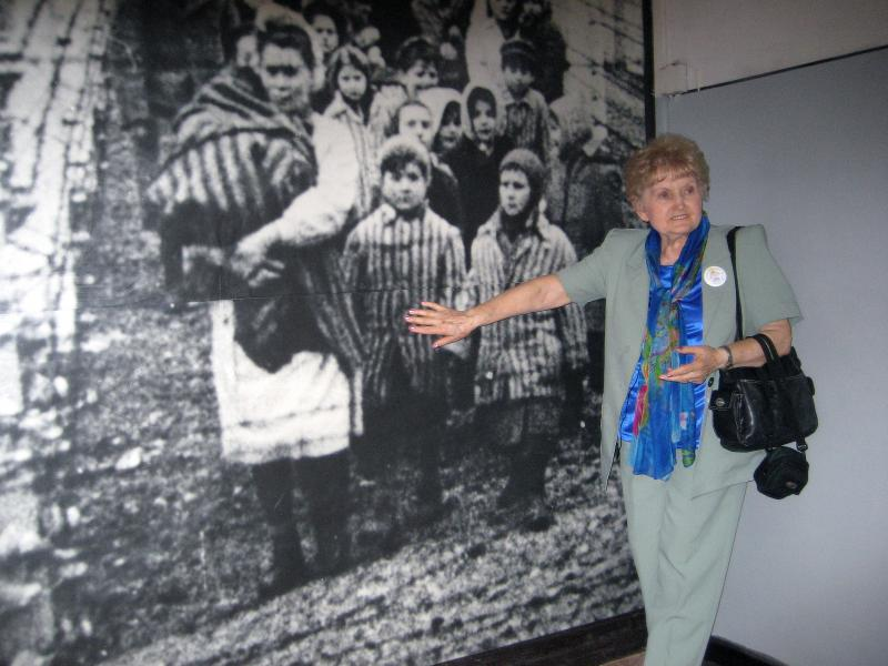 Eva Kor in front of a picture of herself as a child in Auschwitz
