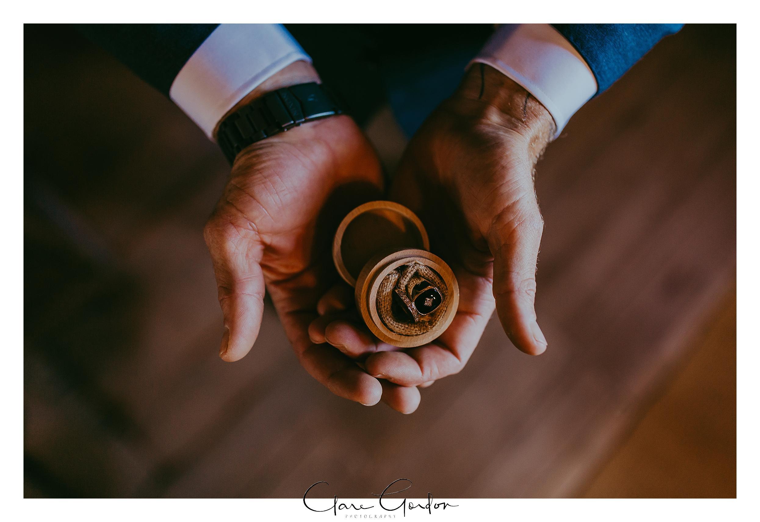 The-Red-Barn-Wedding-Rings-in-grooms-hands.jpg