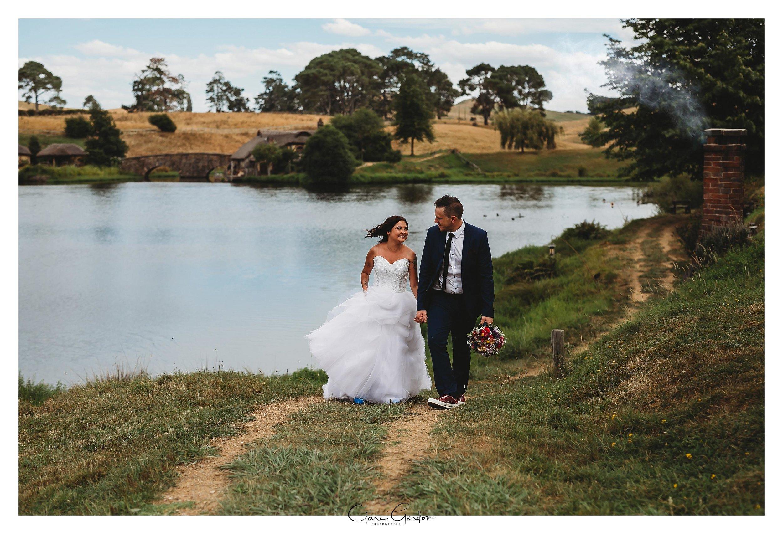 Hobbiton-wedding-photo-Bride-and-groom-Walking-dancing-by-lake (1).jpg