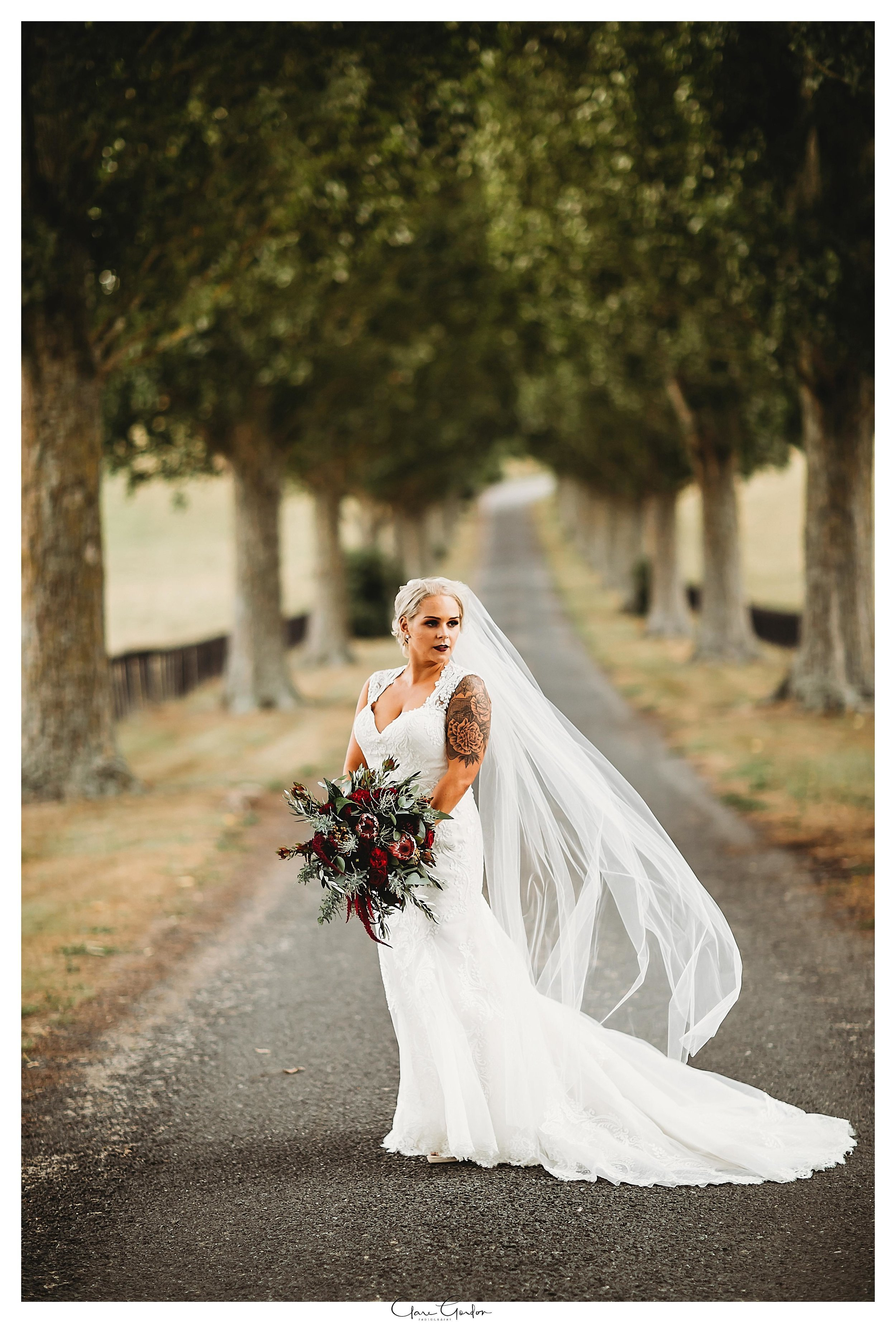 Bride-portrait-on-driveway-red-barn-waikato