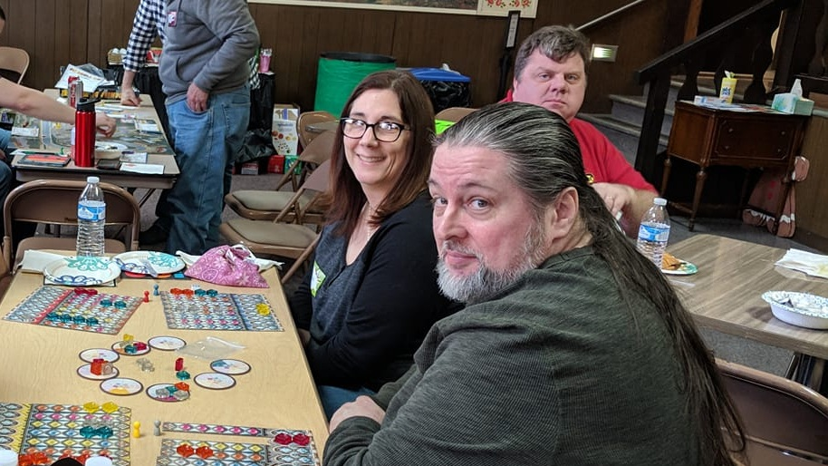 Bill and Angie, and Chris Funk looking in the background. Looks like Bill and Angie are playing Azul: The Stained Glass of Sintra.