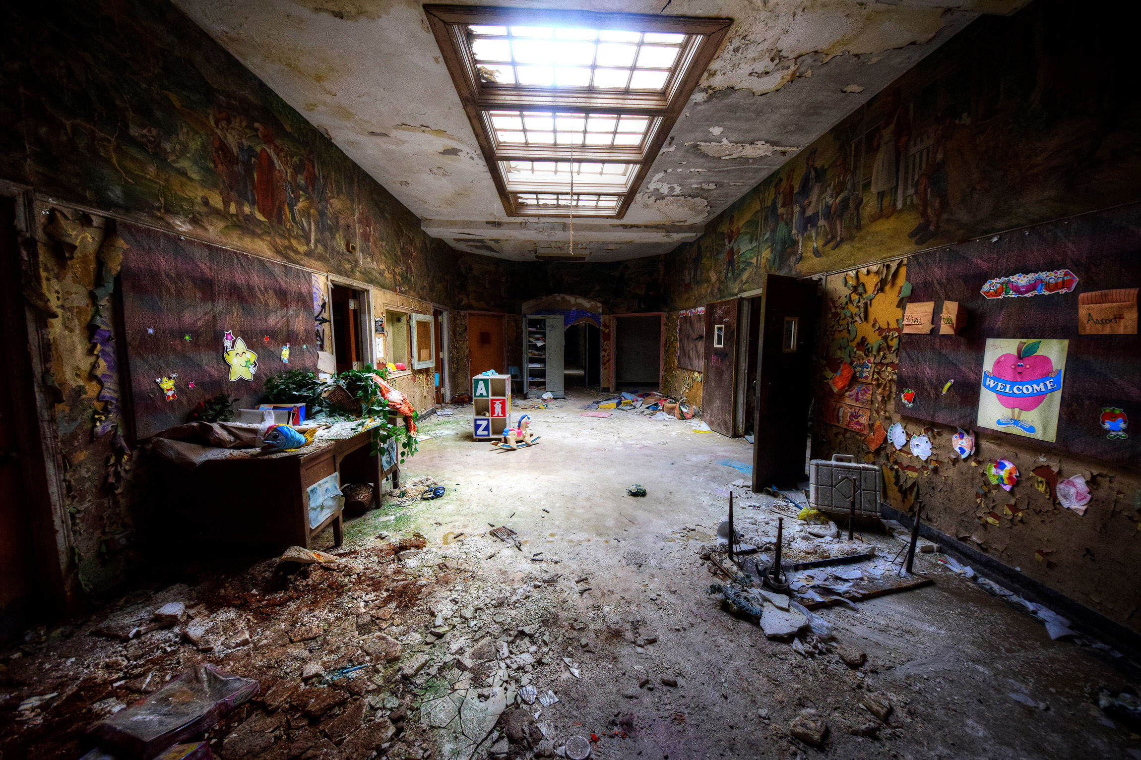 Rocklands Psychiatric Centre-Childrens Block - This is the kids block of this gargantuan site.It got to the stage where I couldn't face any more rooms rammed full of surreal toys (note the weird pumpkin stack toy – that was freaky) and sinister decay. It went on for ages and simply had room after room of treats. As the sun was starting to set we went down into the basement via stairway right next to the entry point. There was a huge room full of antique rotting chairs and an old fashion sign marking 'main tunnel' we shone our torch down the way and couldn't see the end. It would take a week to even give a cursory superficial sweep of this place. It just confirmed to me that the USA is an exploring heaven.I don't think I will ever need to see an abandoned nursery/school/kids psychi unit ever again as this completely over did that whole thing-complete saturation. I don't think you will either, after scrolling through my pictures!