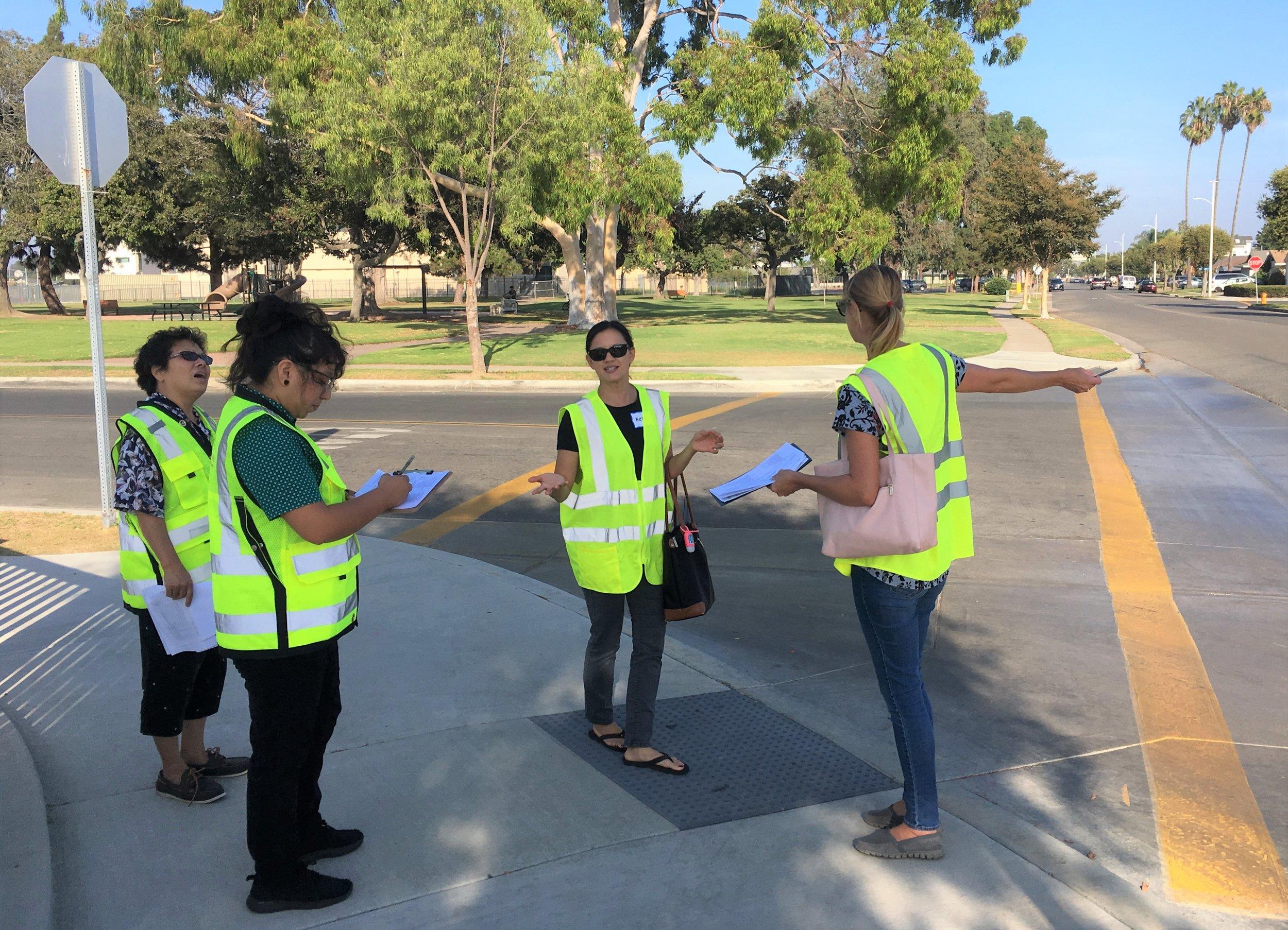 Personal de Cal Walks dirigen a padres en una evaluación de la seguridad peatonal sobre rutas usadas por estudiantes para llegar y salir de la escuela en Huntington Beach.
