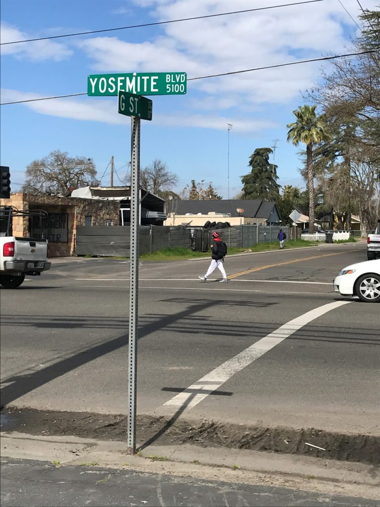 A pedestrian crosses G Street, along Yosemite Boulevard (CA-132), where there are no sidewalks on either end of the crossing.