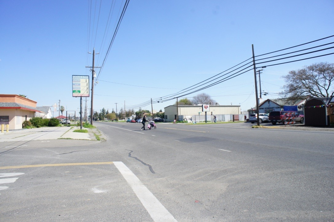 In Empire, a woman with a stroller crosses the highway from the small convenience store back toward the homes on the south side of the highway.