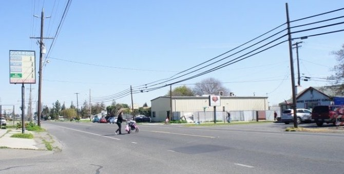 A woman with a stroller crosses the State Route 132 from the small convenience store back toward the homes on the south side of the highway. SB 127 would make sure there would be crosswalks to make this safer for everyone!