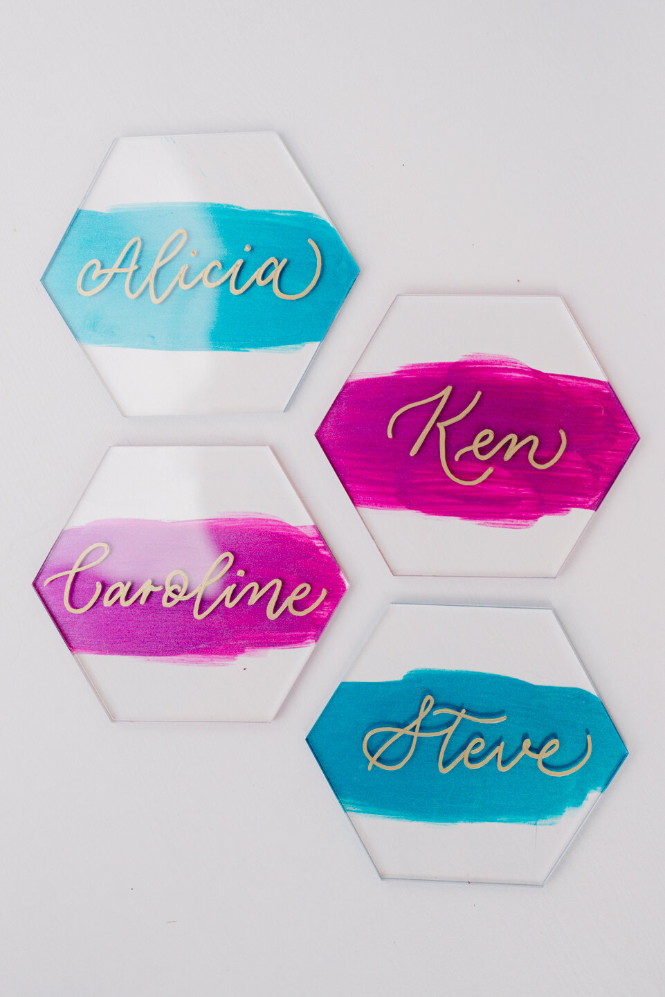 Hexagon acrylic place cards with painted backs, gold ink, and modern calligraphy.