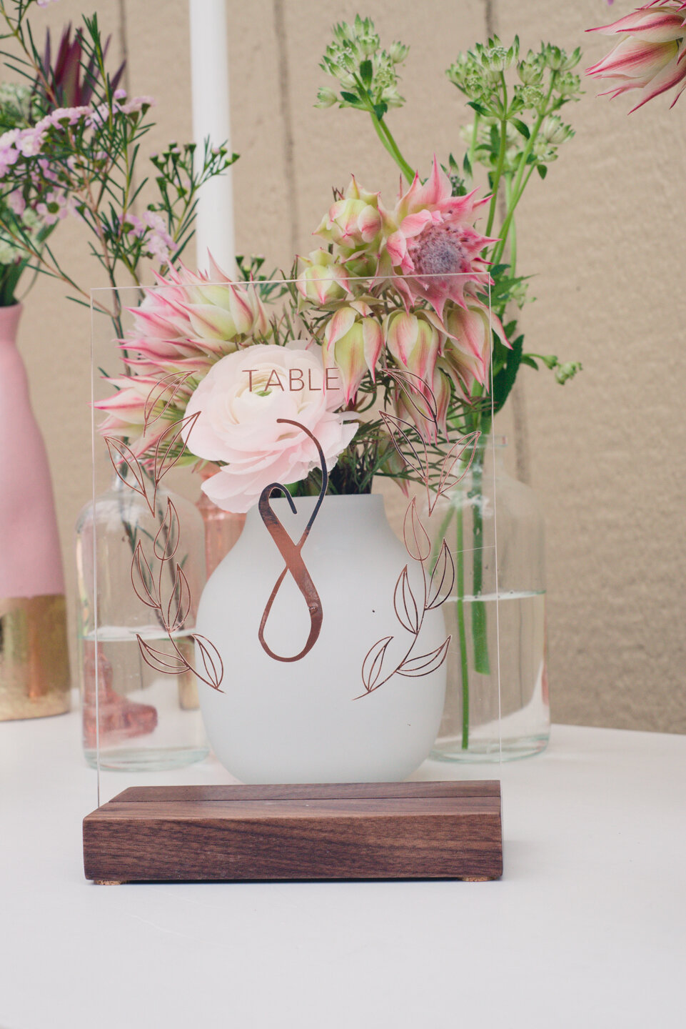 Acrylic table number with rose gold foil and walnut stand. Available as a rental.