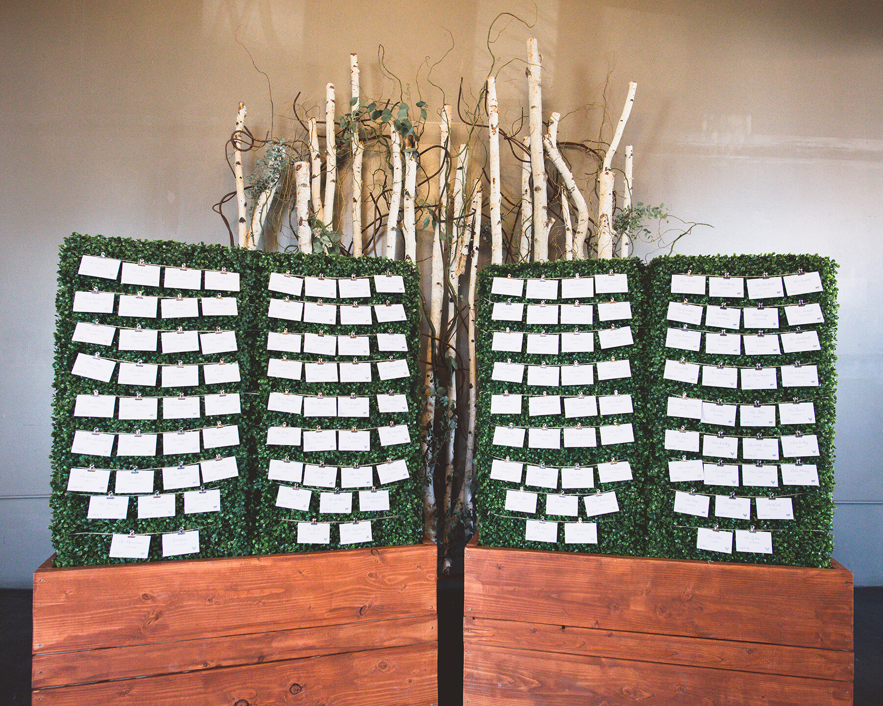 Escort Card display with table numbers and meal selections on a hedge wall.