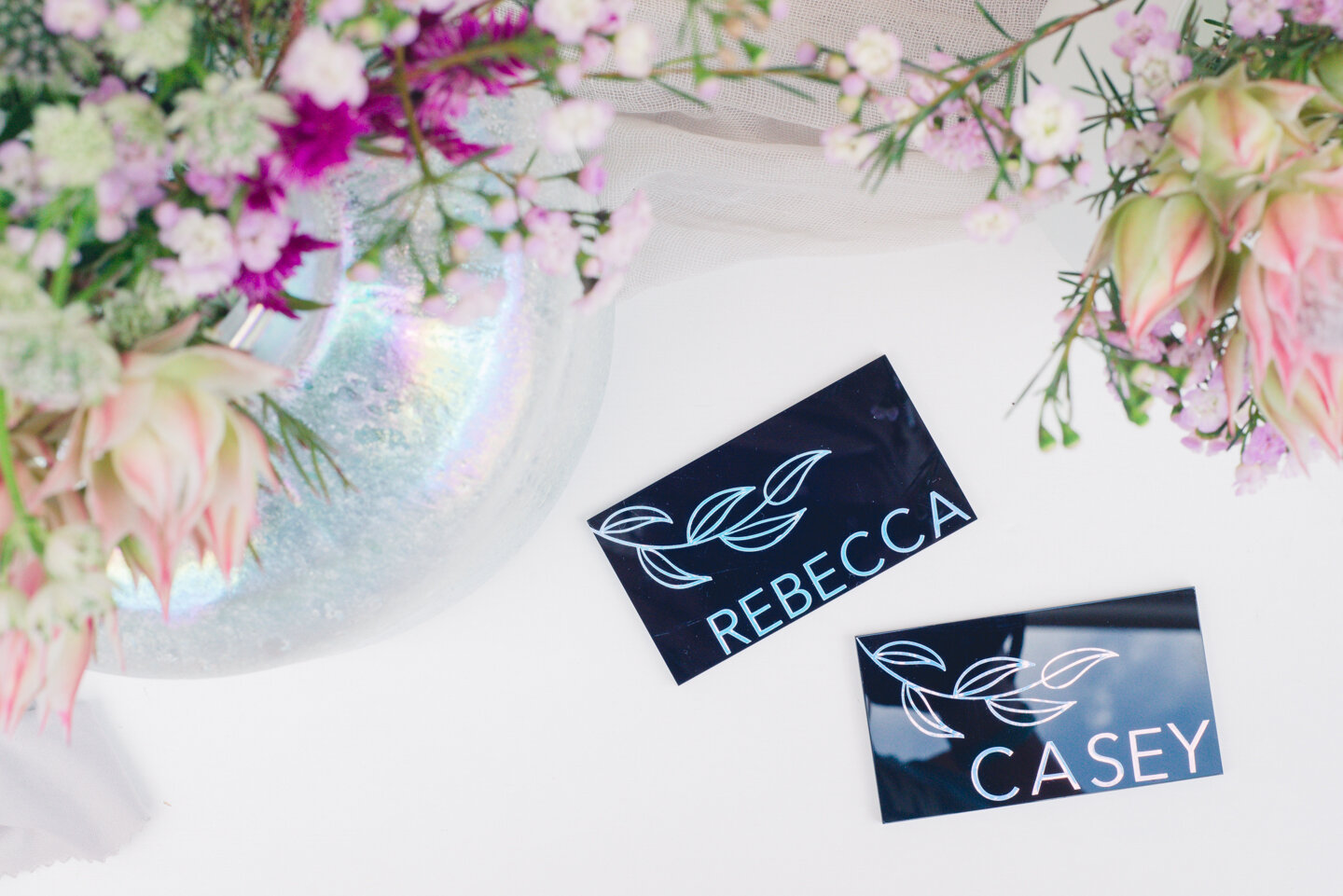 Black acrylic place cards with holographic vinyl and floral elements.