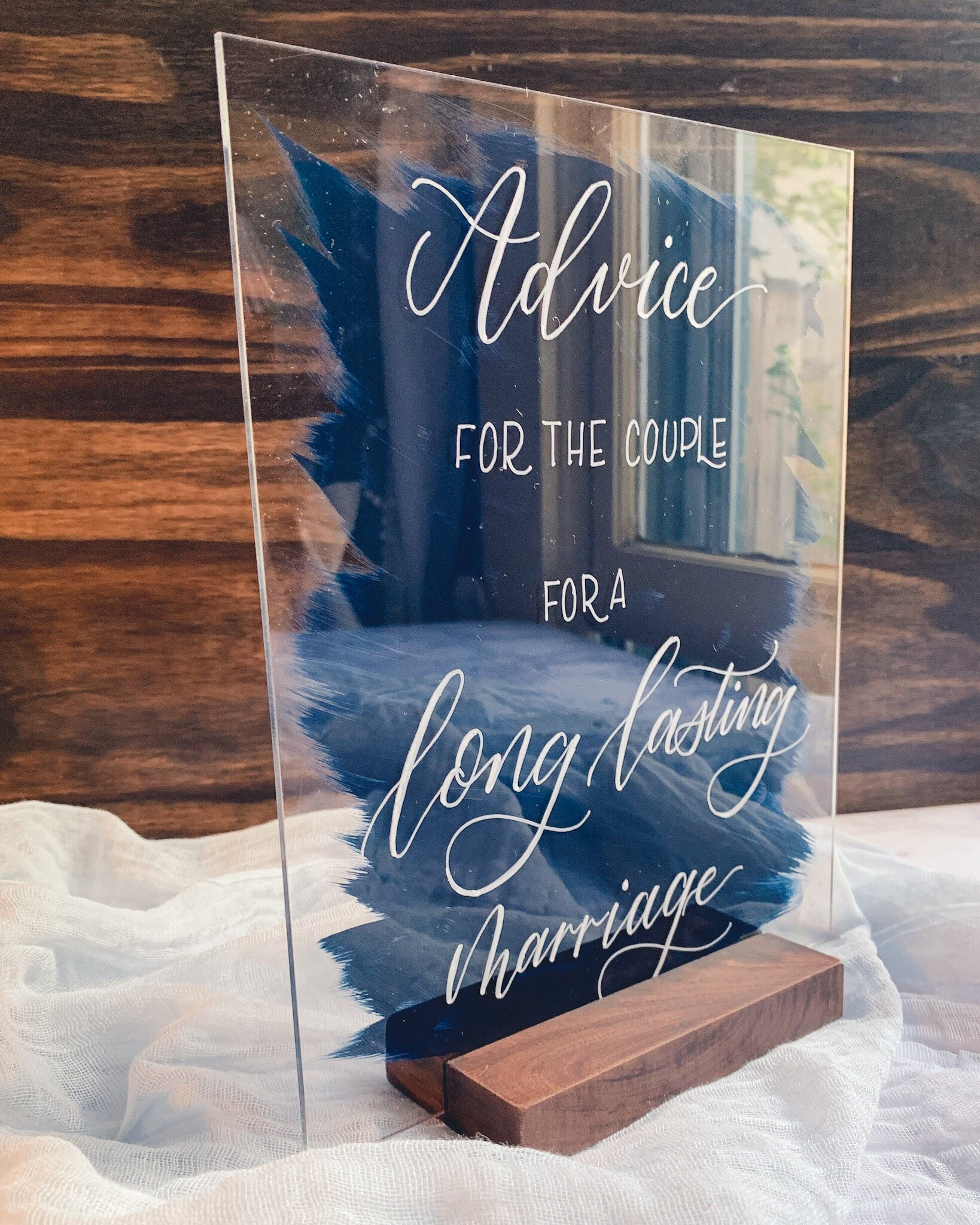 Acrylic sign with painted back and walnut wood stand.