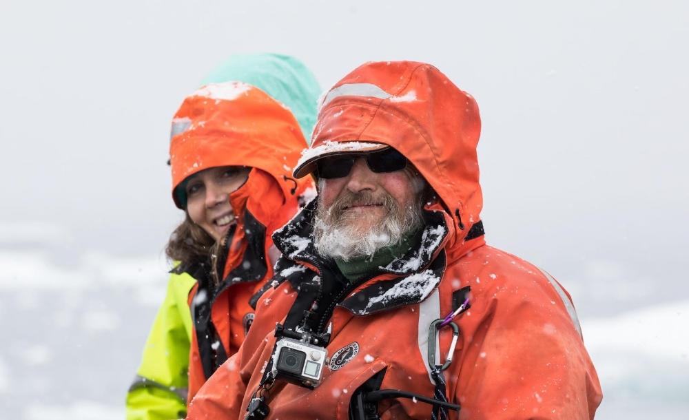 man and woman looking at camera antarctica