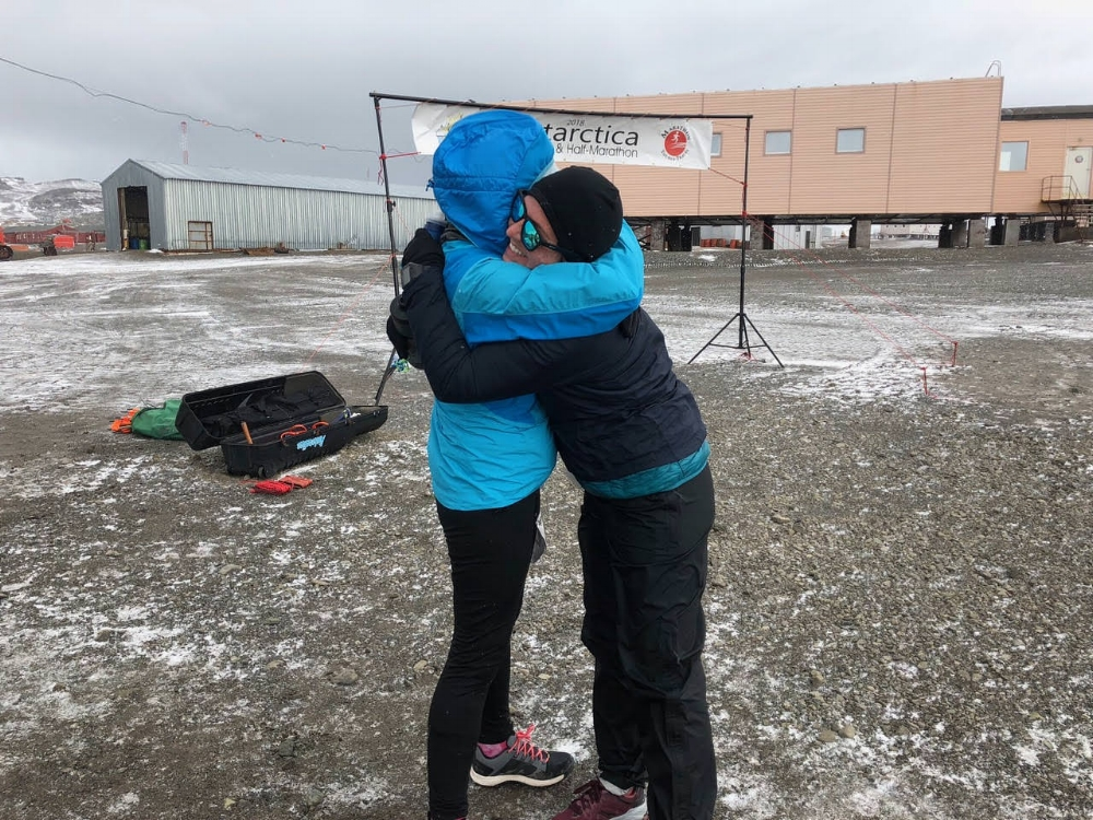 two women hugging end marathon antarctica