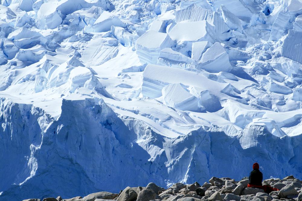 Person sitting in front of glacier neko harbor Antarctica