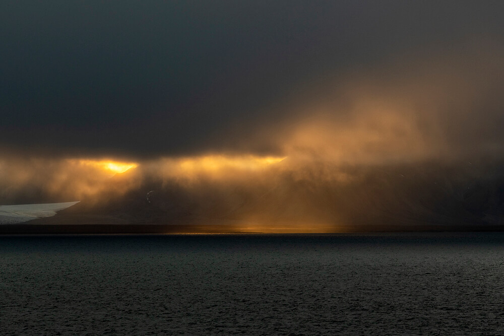 Sunlight breaks through heavy clouds on the coast of Svalbard, Norway.