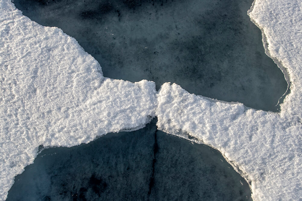 Sea ice forms on the Arctic Ocean, creating abstract patterns.