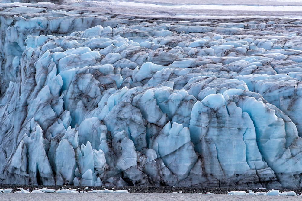 Sand and gravel get caught in ice, forming a marbled effect in the glacier at Yankee Harbor, Antarctica.