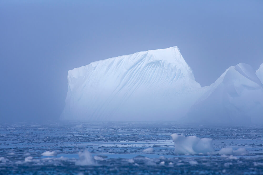 Iceberg in the mist of Antarctica against a blue ocean and sky by CT Productions