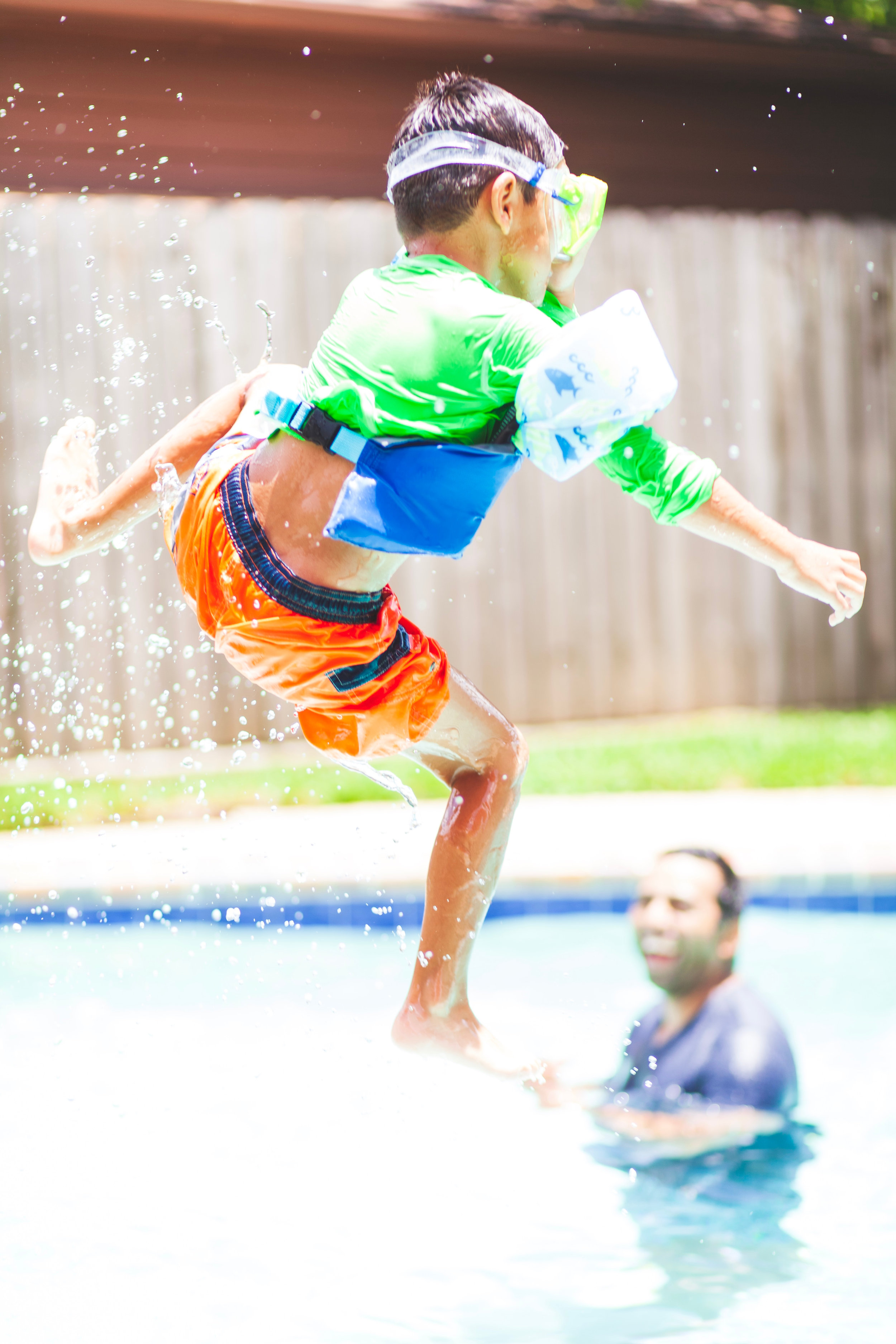 Canva - Boy in Green Crew-neck Shirt and Orange Shorts Jump over Swimming Pool.jpg