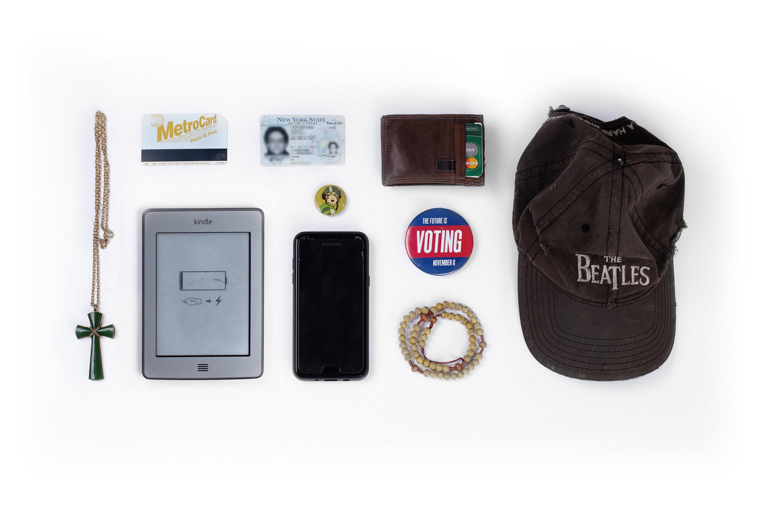 Cross – Metrocard – New York State ID – Wallet – Cap – Ebook Reader – Phone – Pin – Voting Pin – Bracelet